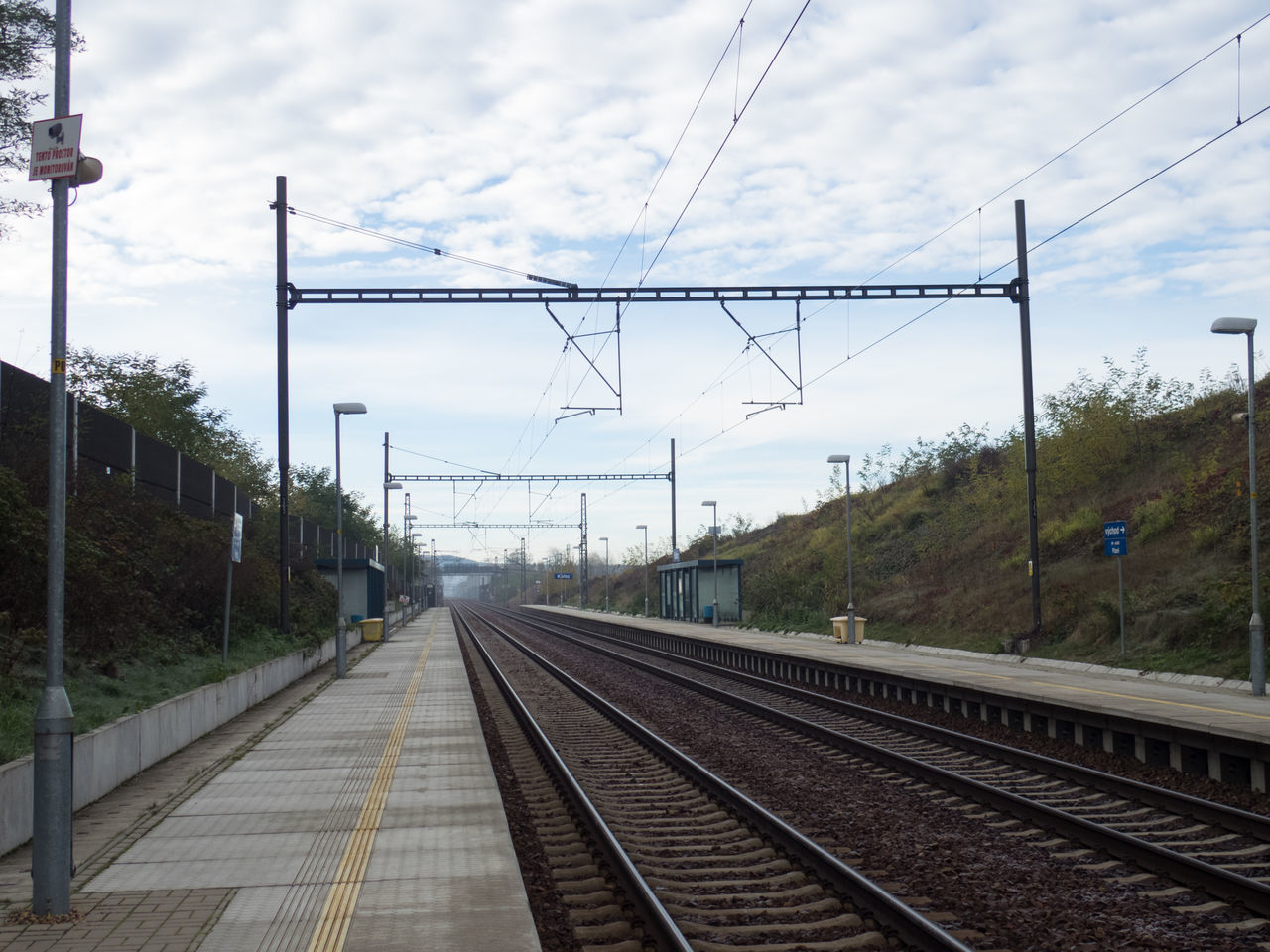 railroad track, cable, rail transportation, transportation, power line, electricity pylon, electricity, power supply, sky, day, cloud - sky, public transportation, connection, outdoors, no people, railway track, nature, technology, tree