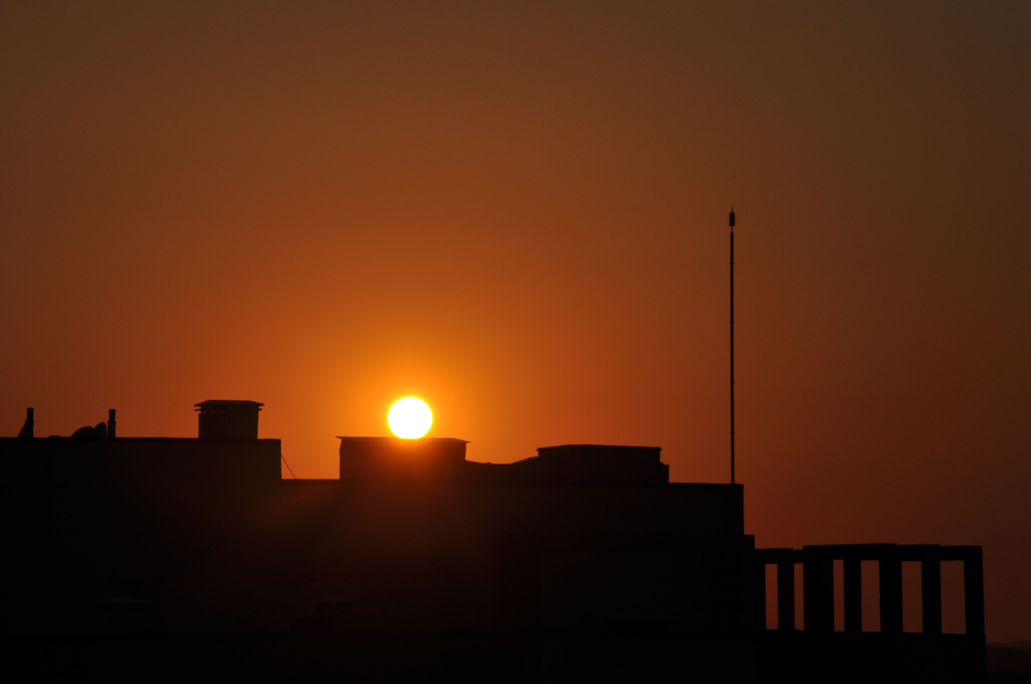 sunset, building exterior, architecture, built structure, sun, silhouette, orange color, copy space, low angle view, clear sky, building, sunlight, house, residential structure, sky, residential building, city, outdoors, no people, nature