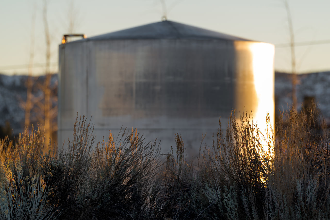 Beauty In Nature Day Field Golden Golden Hour Grass Metal Mountain Mountains Nature No People Outdoors Silver - Metal Sky Sky And Clouds Steel Steel Structure  Sunset Tallgrass Water Watertank Weeds