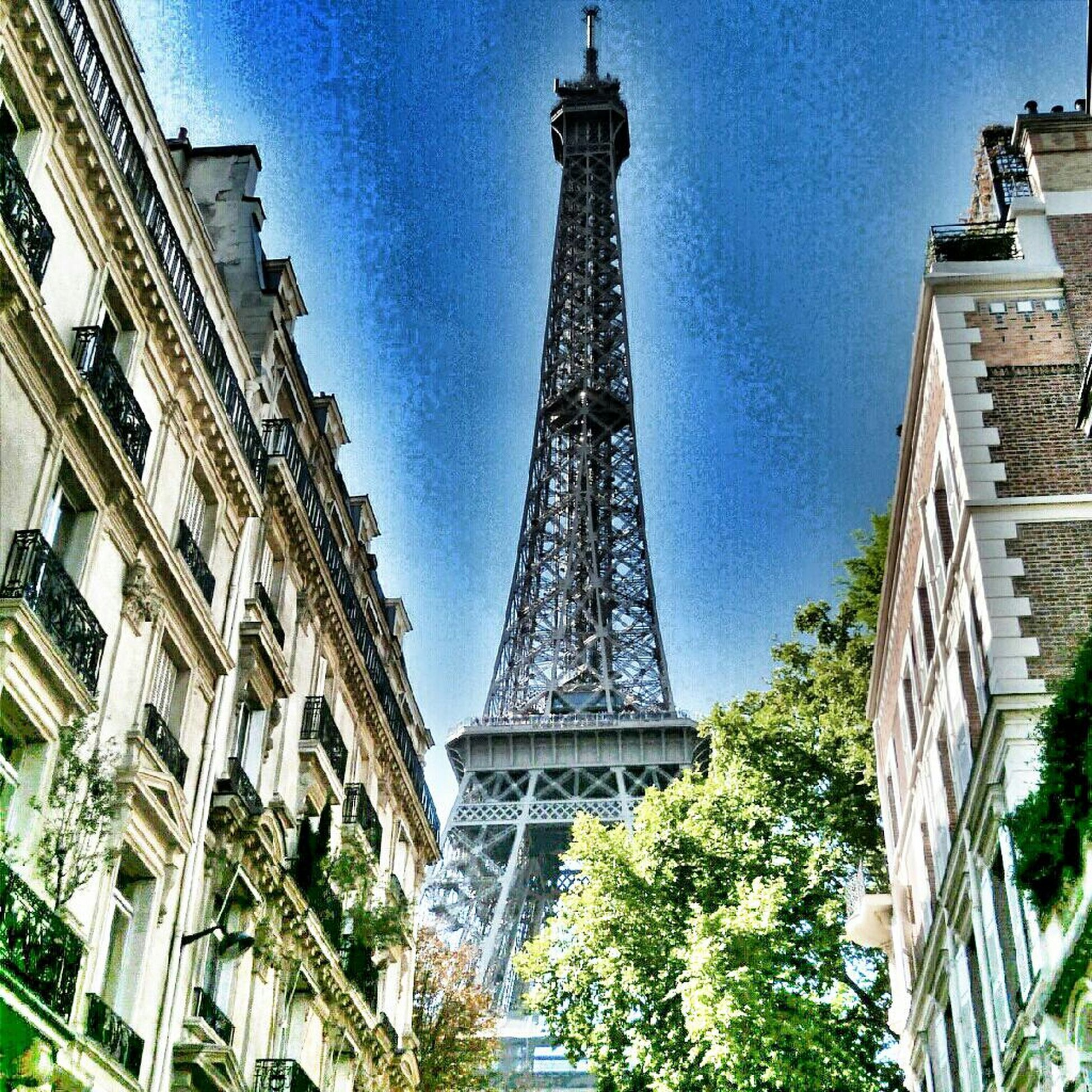 architecture, built structure, building exterior, tower, tall - high, low angle view, city, famous place, travel destinations, capital cities, international landmark, eiffel tower, tourism, tree, sky, travel, blue, tall, skyscraper, day