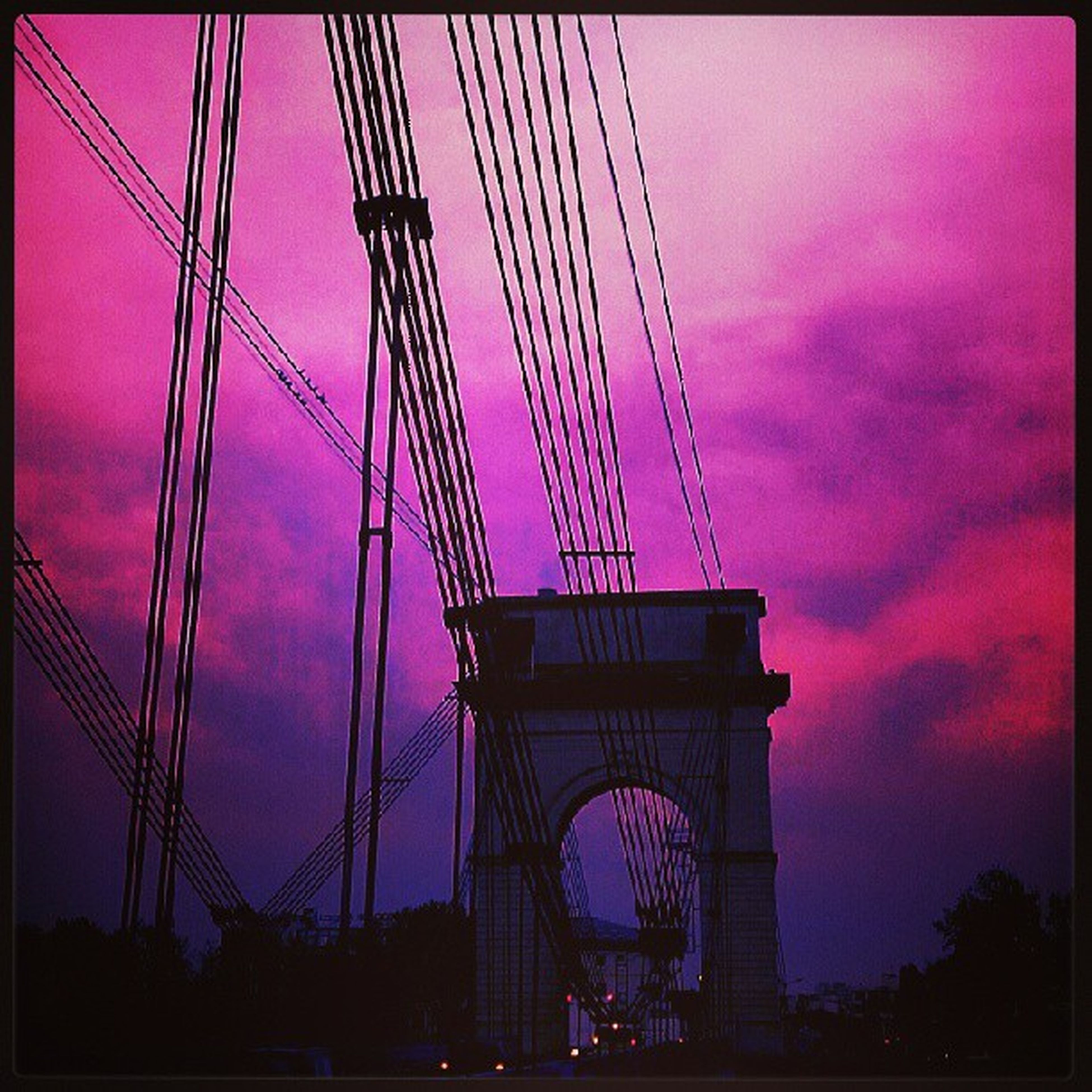 transfer print, sky, built structure, architecture, auto post production filter, low angle view, connection, sunset, cloud - sky, bridge - man made structure, engineering, silhouette, transportation, suspension bridge, cloud, city, travel destinations, outdoors, cloudy, tall - high