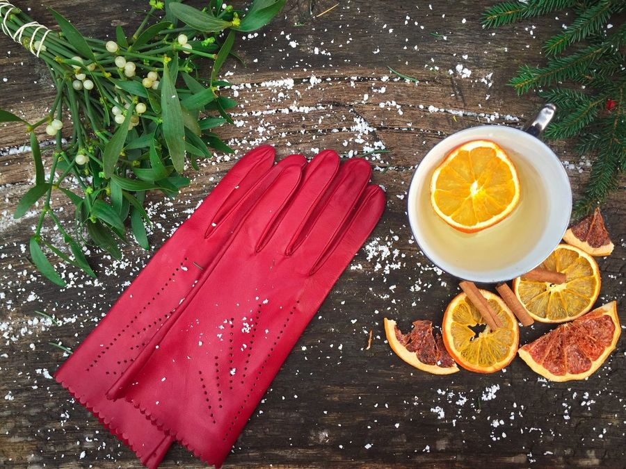 Red gloves near a mug of orange tea with dried orange slices beside and mistletoe on snowy table High Angle View Plant Food And Drink No People Freshness Day Winter Cold Snow Table Rustic Wooden Table Gloves Red Gloves Mistletoe Cup Drink Oranges Dried Slices Tea Orange Tea Flat Lay Citrus