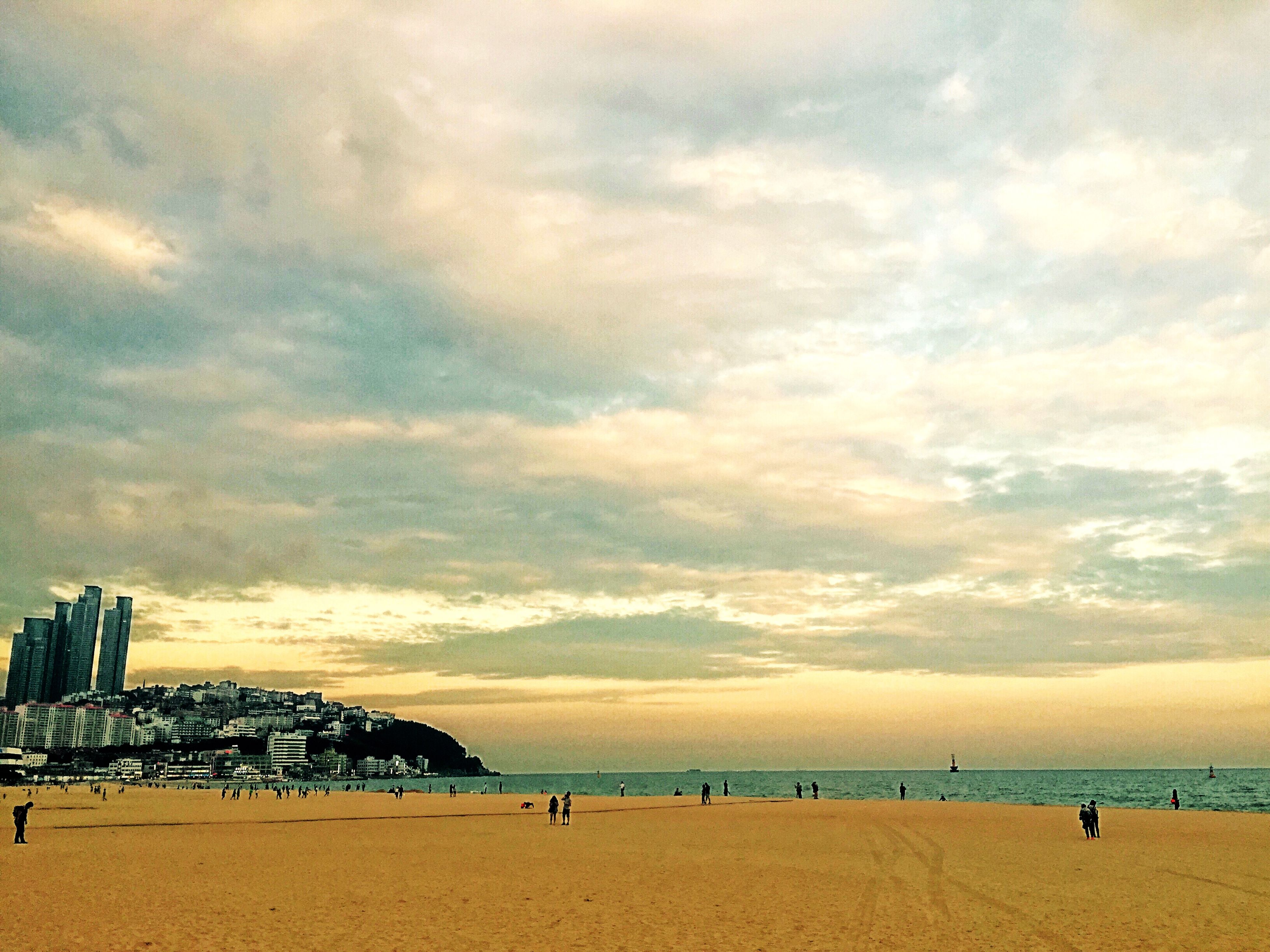beach, sea, sky, shore, built structure, water, cloud - sky, architecture, sand, building exterior, horizon over water, large group of people, vacations, lifestyles, scenics, leisure activity, cloud, cloudy, nature