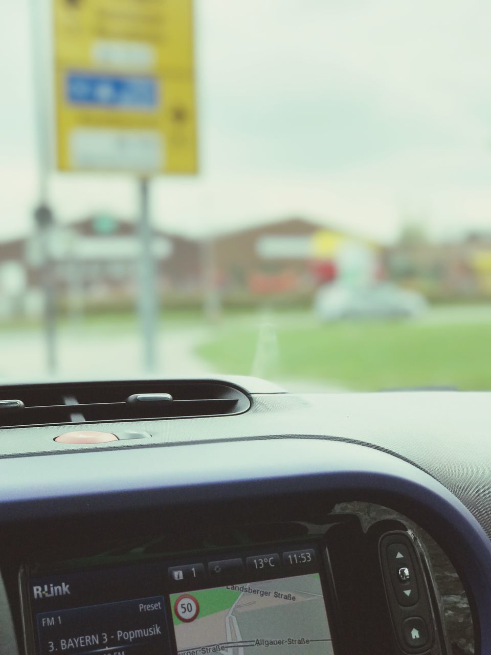 car, land vehicle, dashboard, windshield, text, transportation, focus on foreground, steering wheel, no people, day, close-up, outdoors, speedometer
