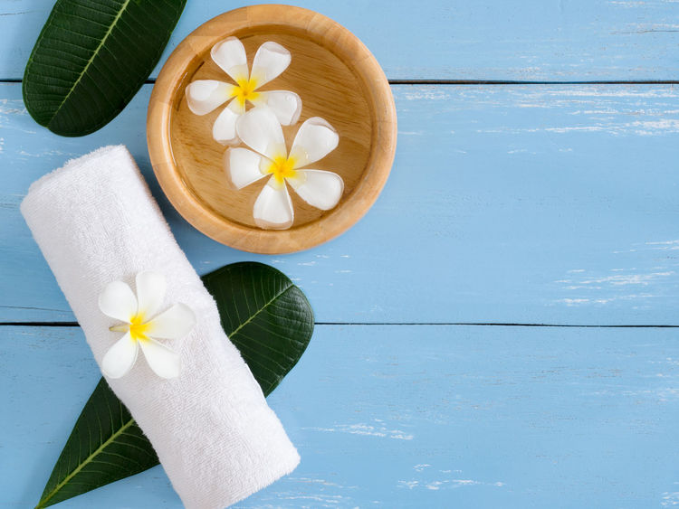 Spa products,white towel with Plumeria flower and leaf on blue wooden table with copy space. Aromatherapy Copy Space Leaf 🍂 Peace Plumeria Relaxing Aroma Beauty Beauty In Nature Clean Cosmetics Flower Freshness Leaf Massage Moisturizer Nature Petal Product Scrub Skincare Spa Towel Treatment Water