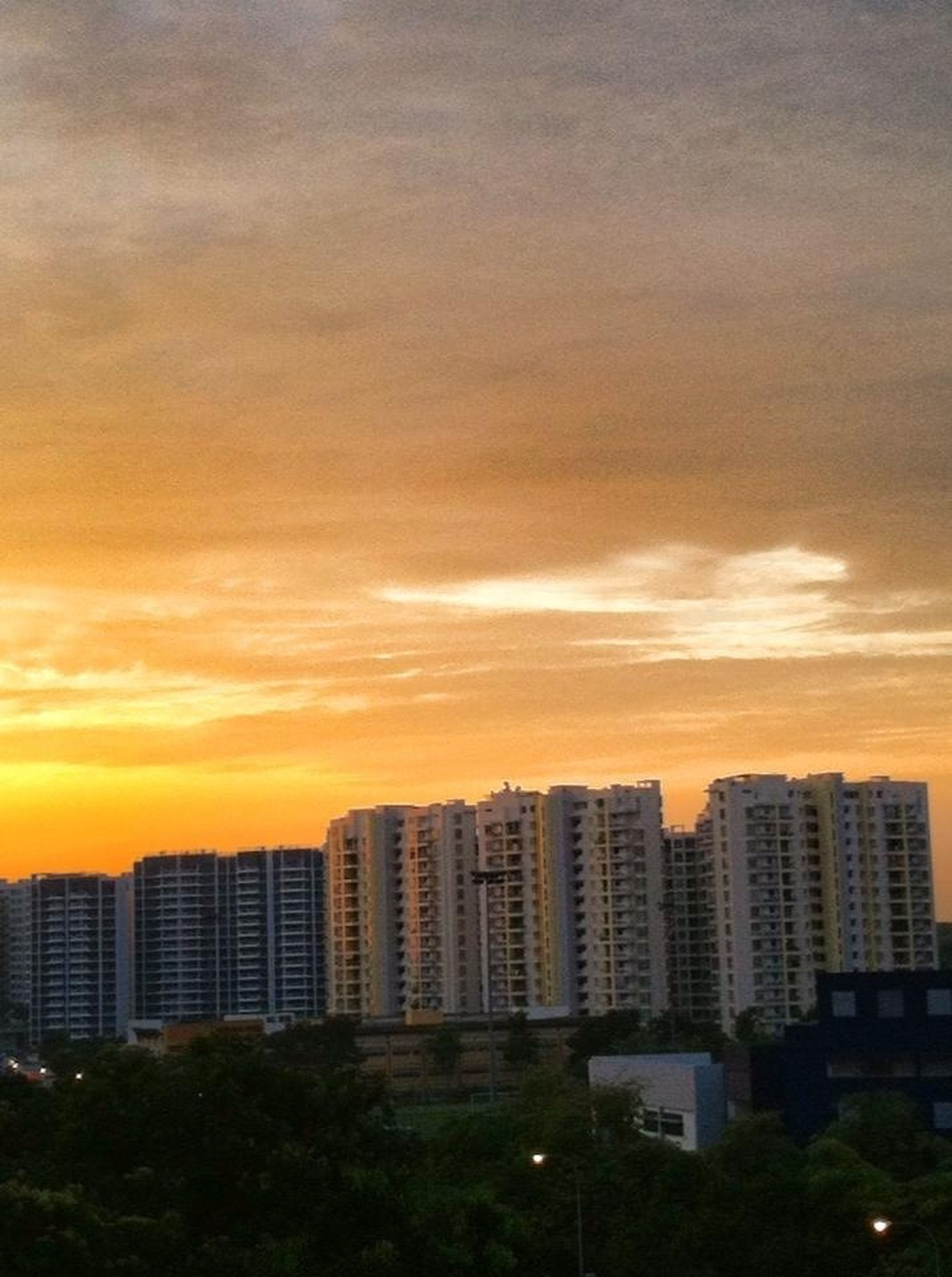building exterior, architecture, built structure, sunset, city, sky, orange color, cityscape, cloud - sky, residential building, building, skyscraper, residential structure, residential district, modern, office building, city life, tall - high, outdoors, cloudy