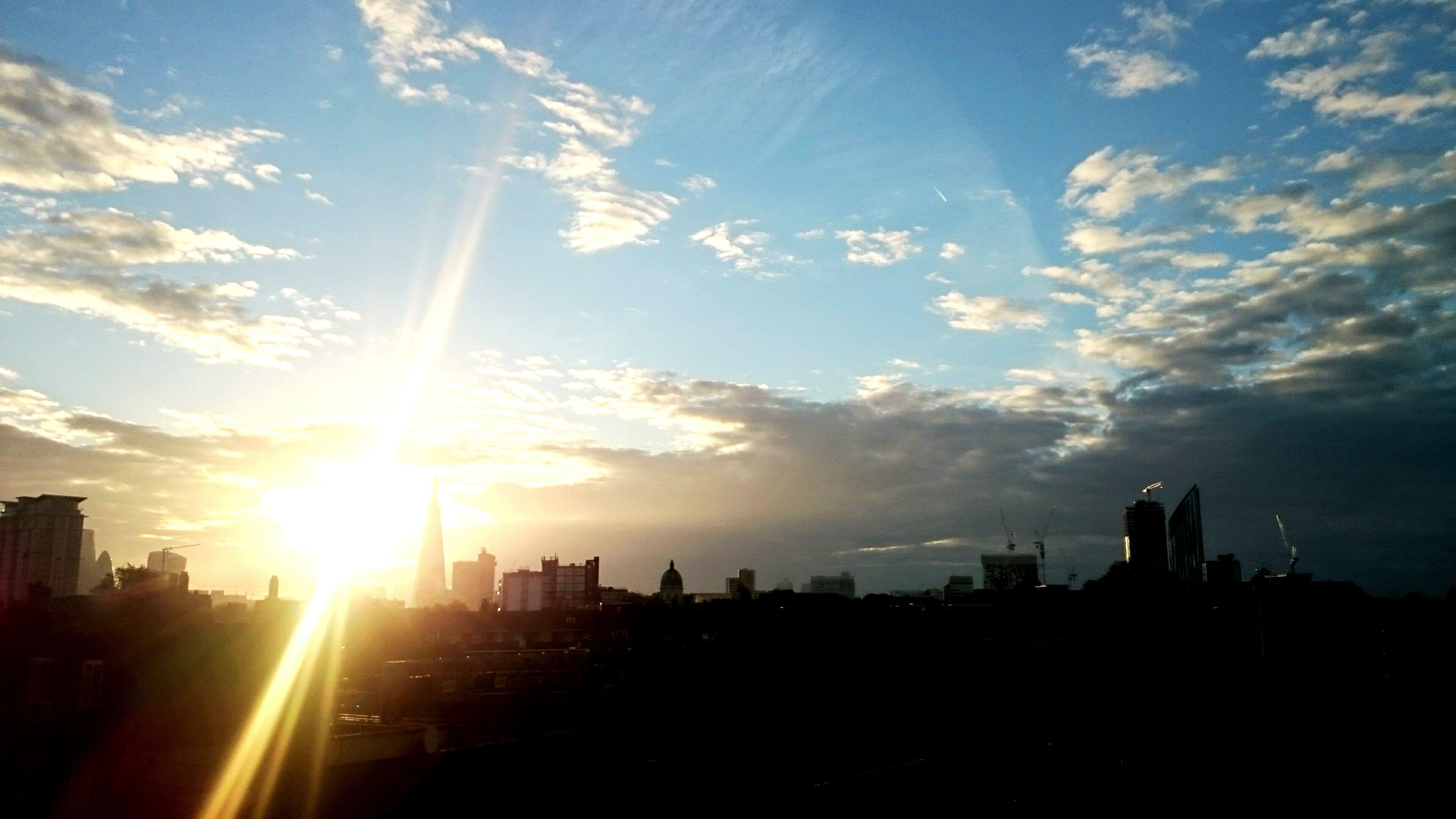 sun, building exterior, sunbeam, sunset, architecture, built structure, silhouette, sunlight, sky, city, cloud - sky, lens flare, cityscape, cloud, building, bright, skyscraper, outdoors, urban skyline, nature