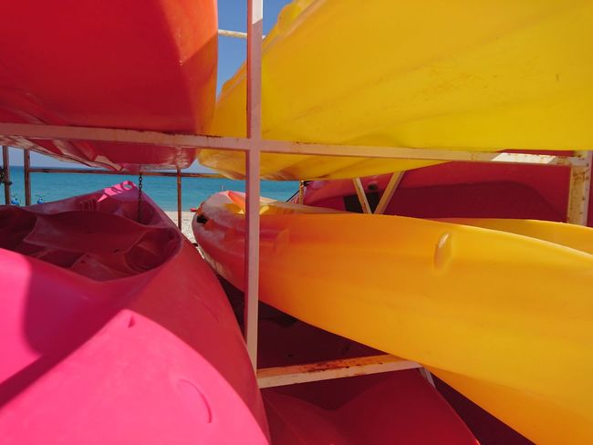 Canoes stacked Canoe Canoes Beach Close-up Red Yellow Pink Color Travel Colors And Patterns Sea Sports Detail Color Vibrant Color Multi Colored Water