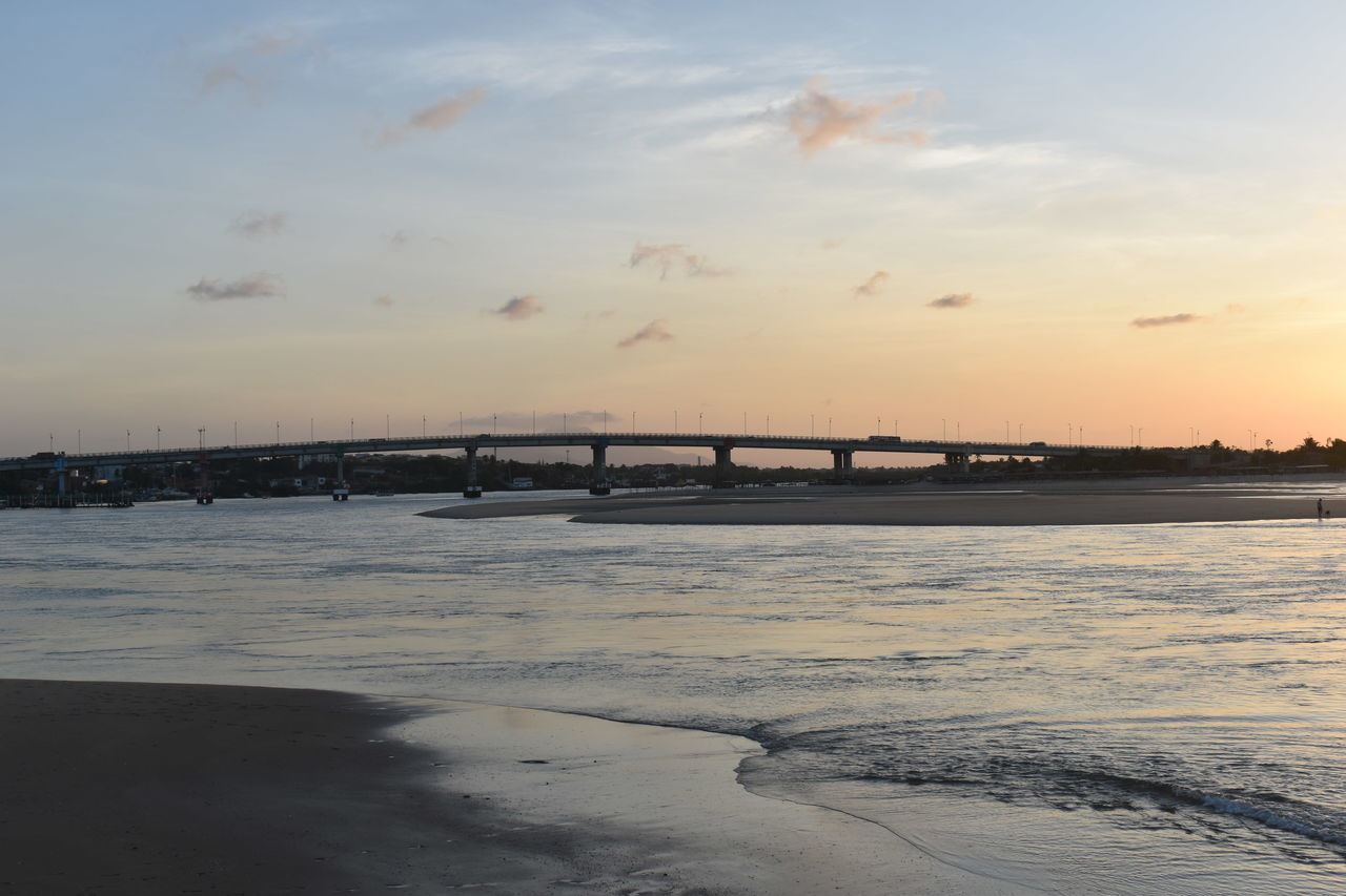 sunset, water, bridge - man made structure, sky, built structure, architecture, nature, connection, sea, beauty in nature, outdoors, cloud - sky, scenics, travel destinations, no people, beach, cold temperature, city, day