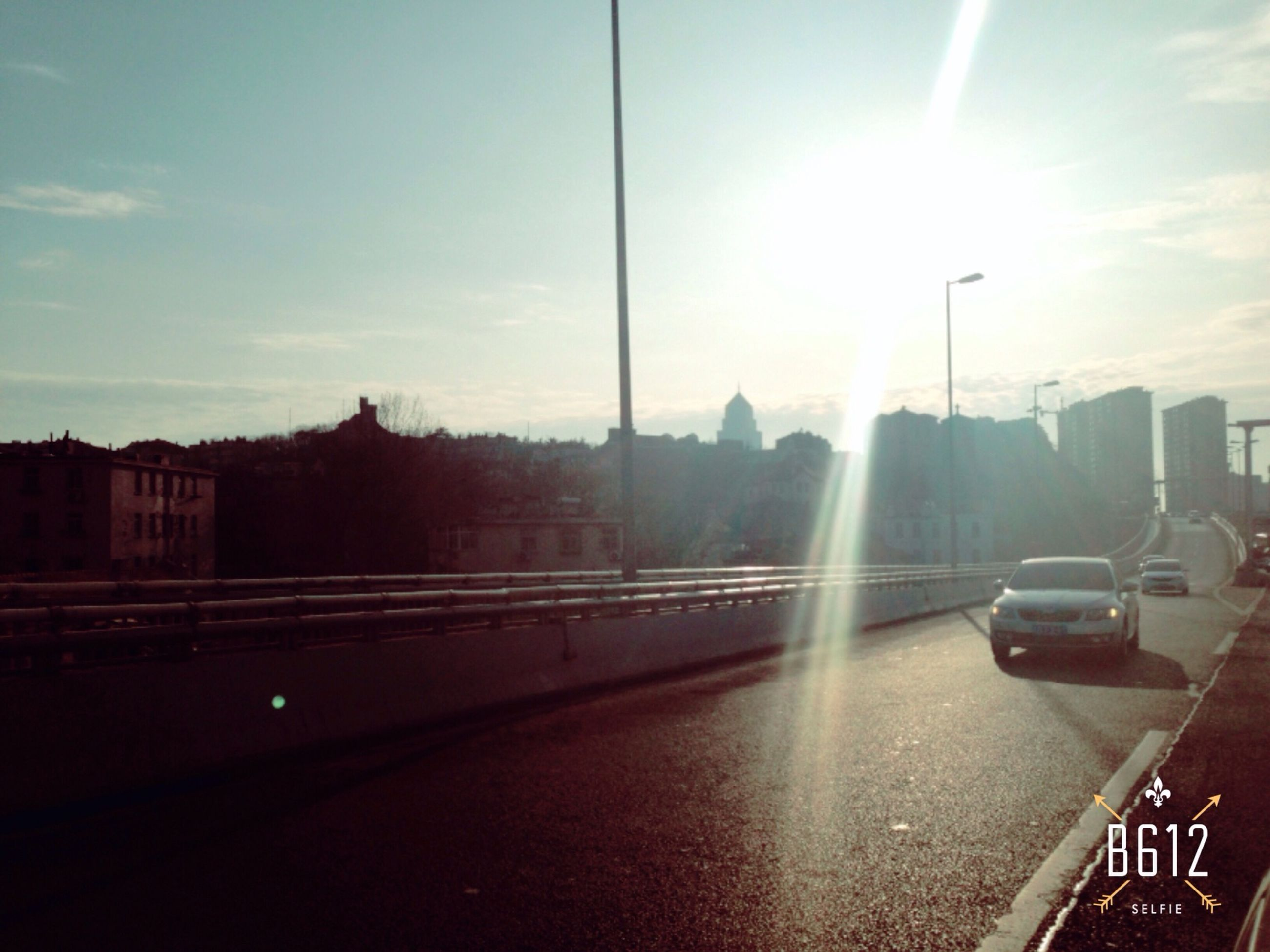 building exterior, architecture, sun, built structure, city, transportation, sky, sunlight, car, mode of transport, sunbeam, reflection, water, sunset, land vehicle, street, lens flare, road, no people, outdoors