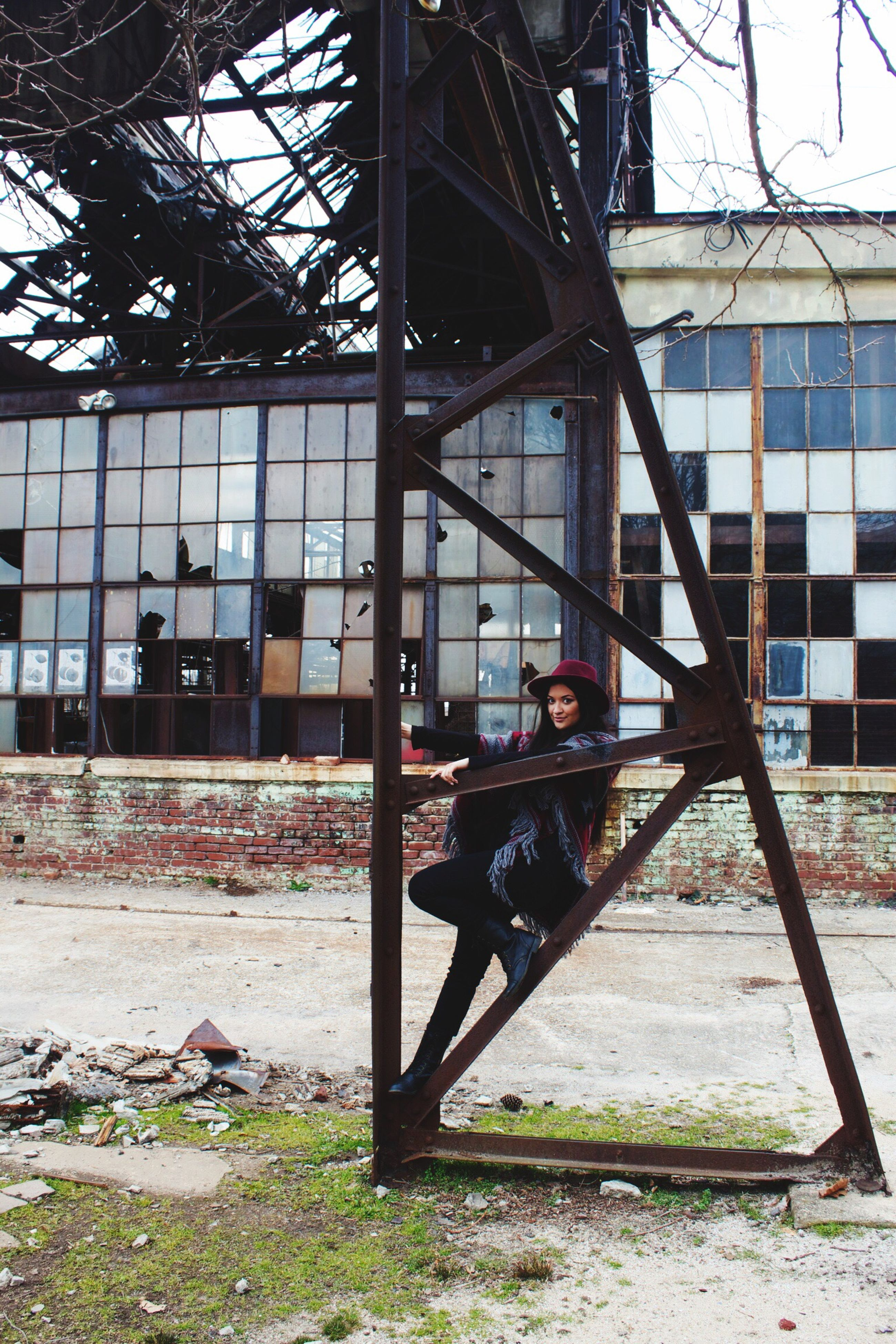 architecture, built structure, building exterior, lifestyles, leisure activity, window, person, young adult, abandoned, day, standing, full length, casual clothing, building, damaged, graffiti, bare tree, glass - material