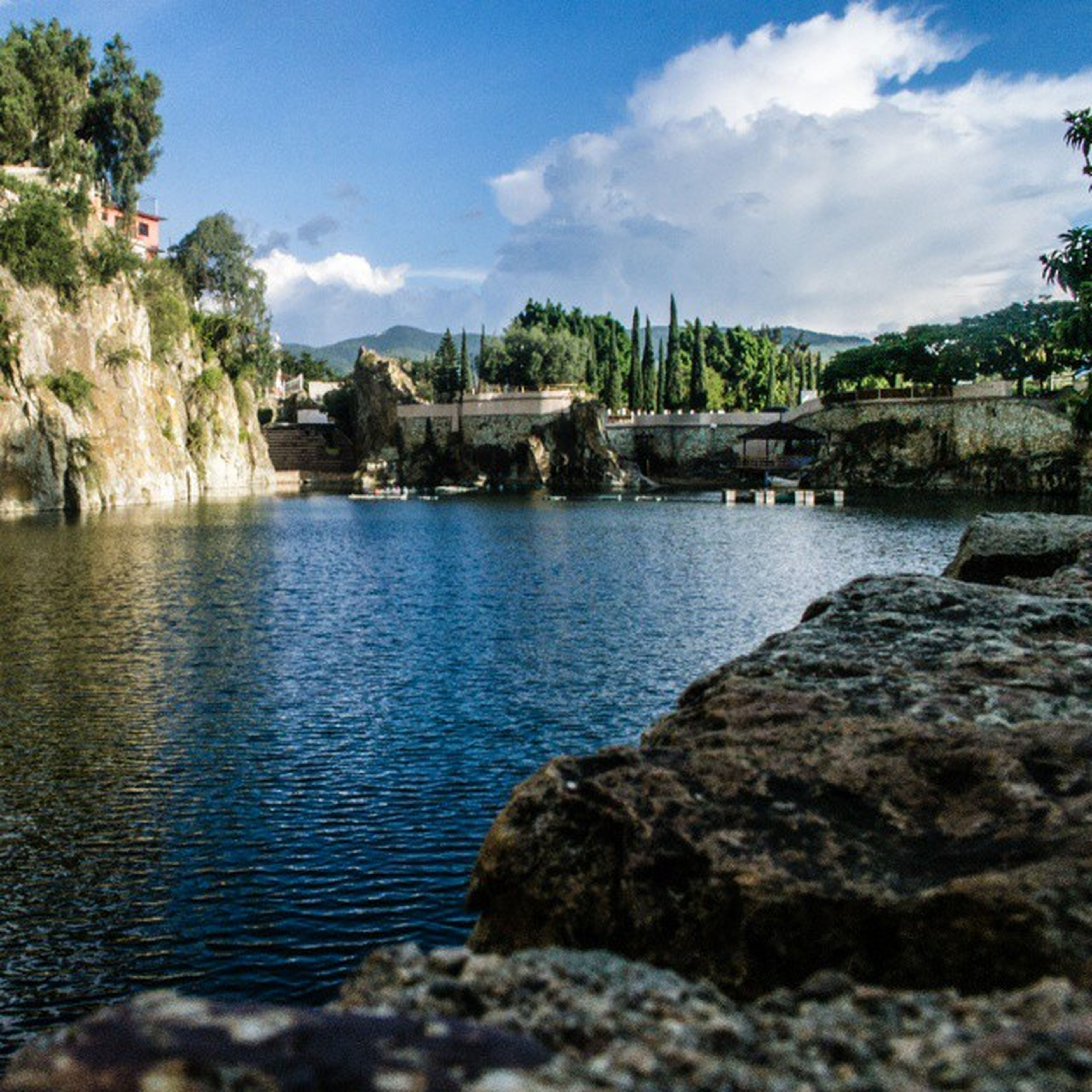 water, tree, sky, tranquil scene, tranquility, rock - object, scenics, nature, beauty in nature, cloud, cloud - sky, waterfront, rippled, river, lake, stone - object, day, idyllic, rock, outdoors