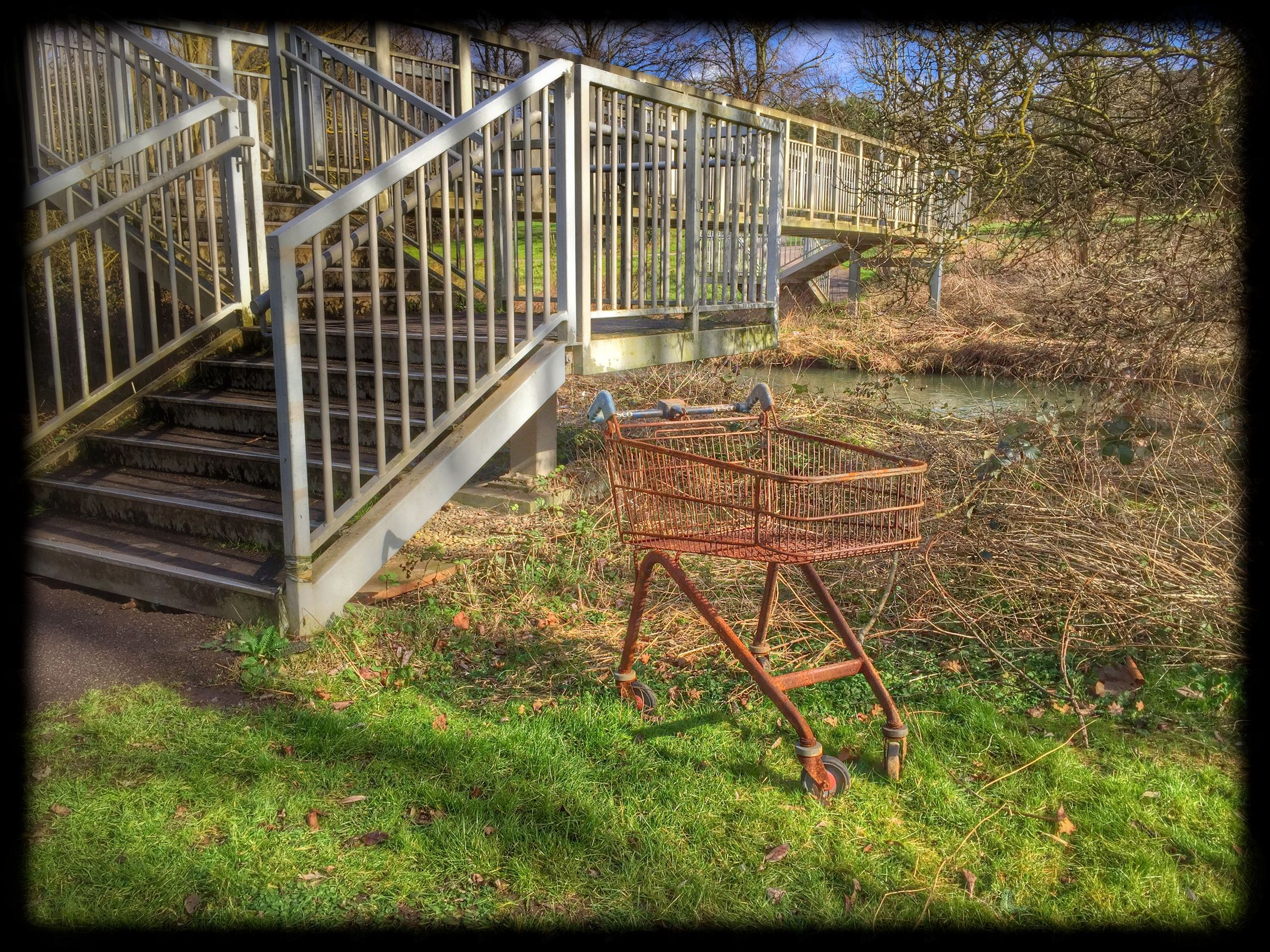 Rusty Shopping Trolley by a River Bridge