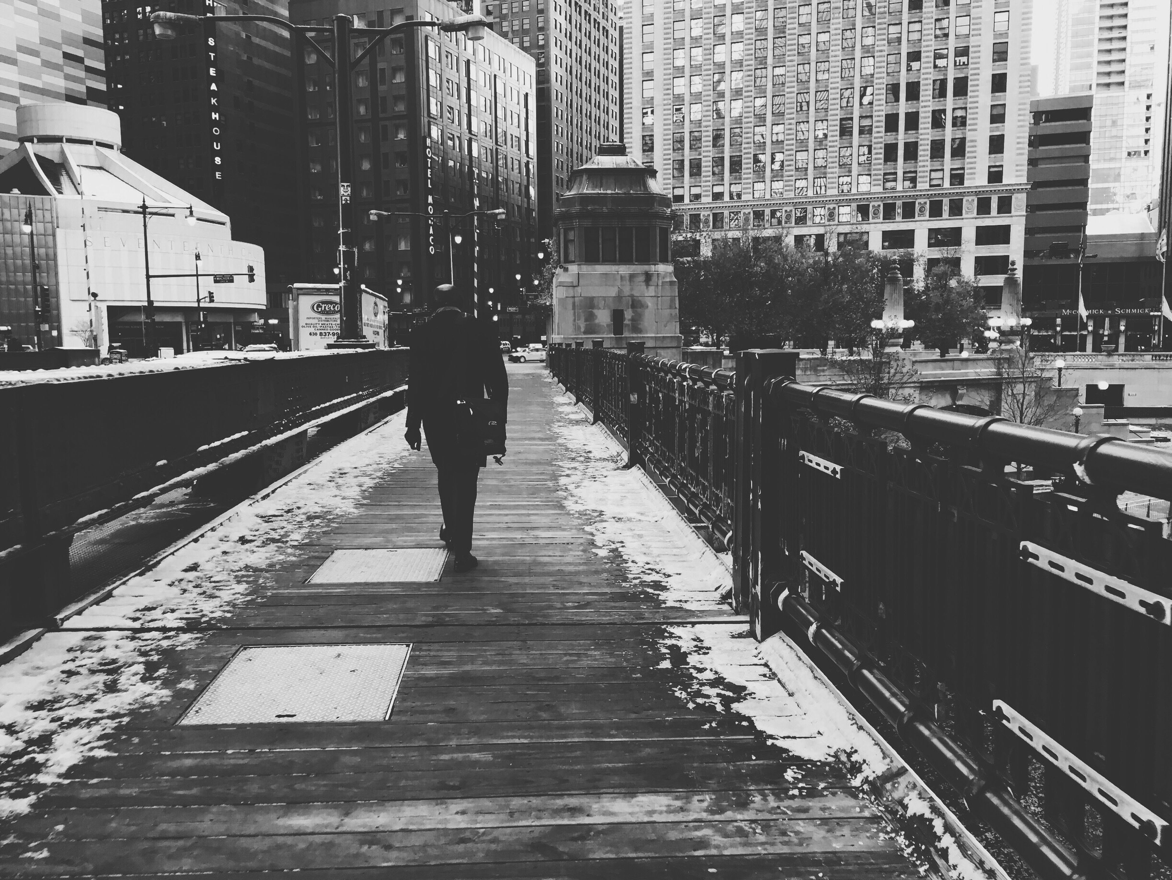 building exterior, architecture, built structure, city, walking, full length, lifestyles, men, the way forward, rear view, city life, railroad track, person, transportation, leisure activity, railing, building, street
