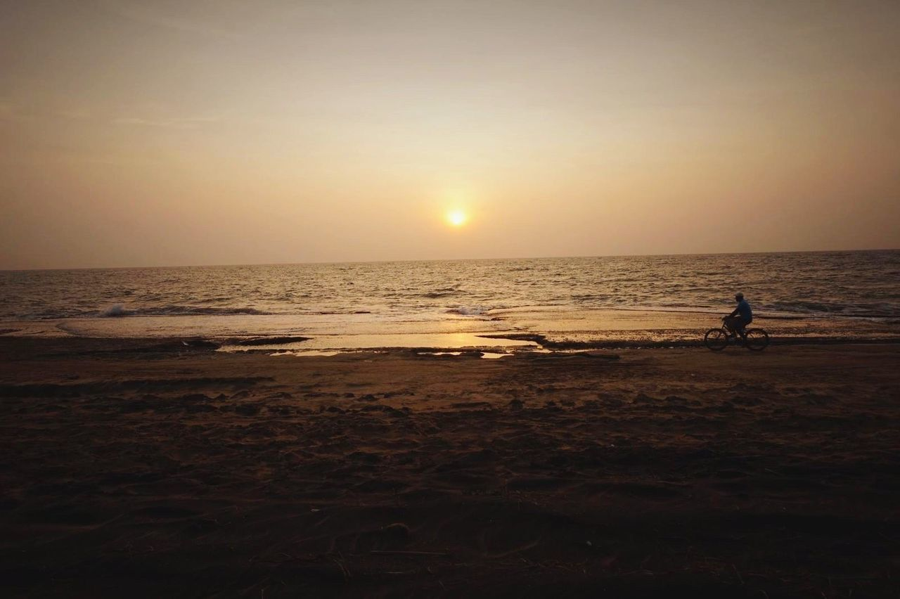 sea, sunset, beach, horizon over water, silhouette, water, scenics, nature, beauty in nature, sun, real people, tranquil scene, one person, tranquility, sky, standing, sand, outdoors, men, full length, clear sky, wave, day, people