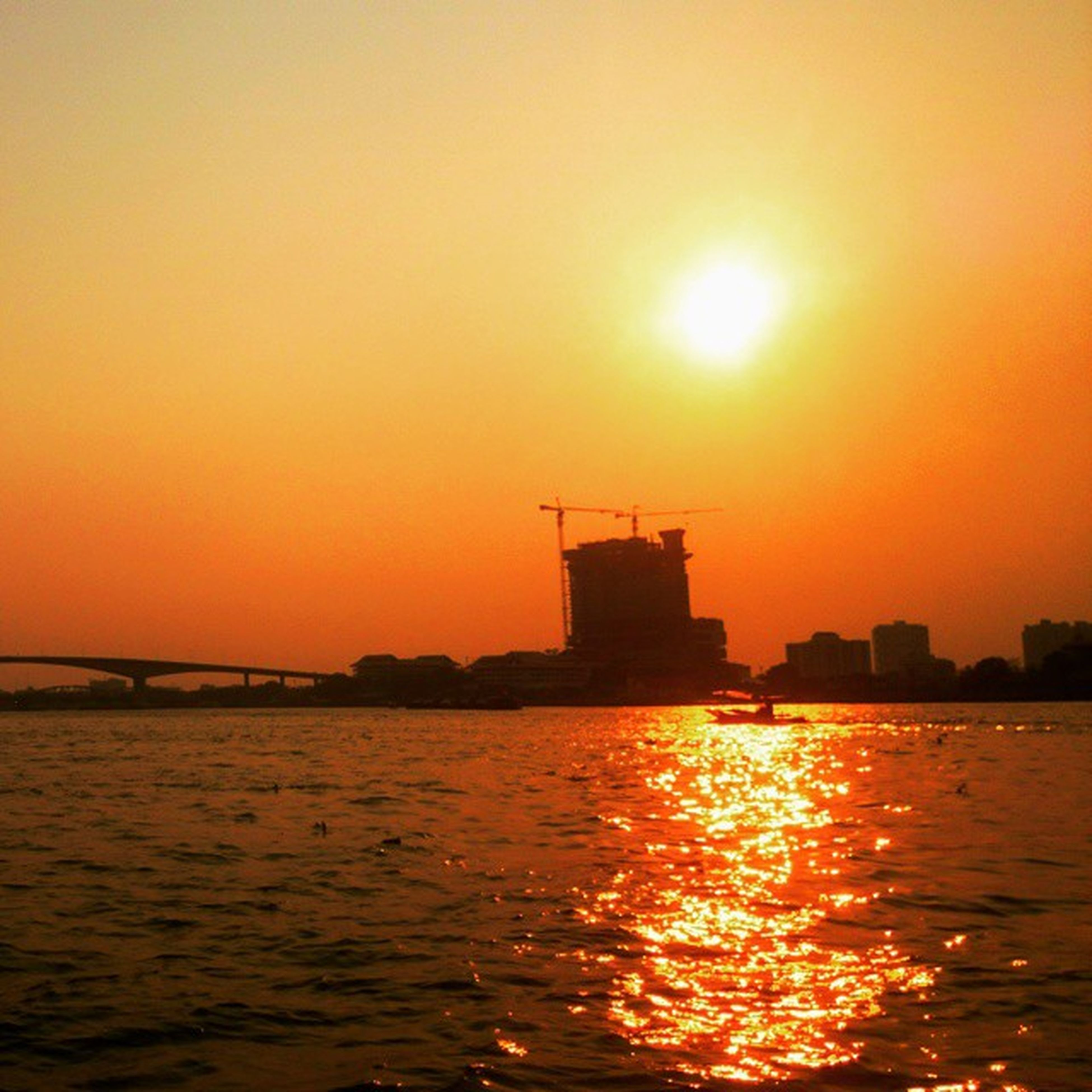 sunset, sun, water, waterfront, orange color, silhouette, built structure, architecture, building exterior, sea, sunlight, nautical vessel, rippled, scenics, reflection, beauty in nature, transportation, nature, clear sky, river