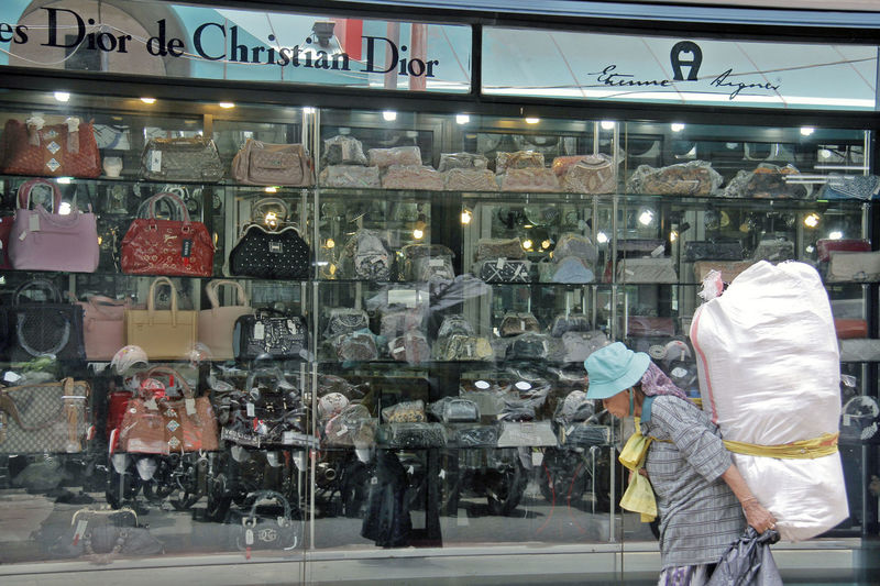 a homless women walking in front of a expensive and famous women bag in jakarta Bags Brand Business Collections Culture Cultures Fashion Bag Fashionista For Sale Homless Indoors  Large Group Of Objects Satires Still Life Variation Women Bag