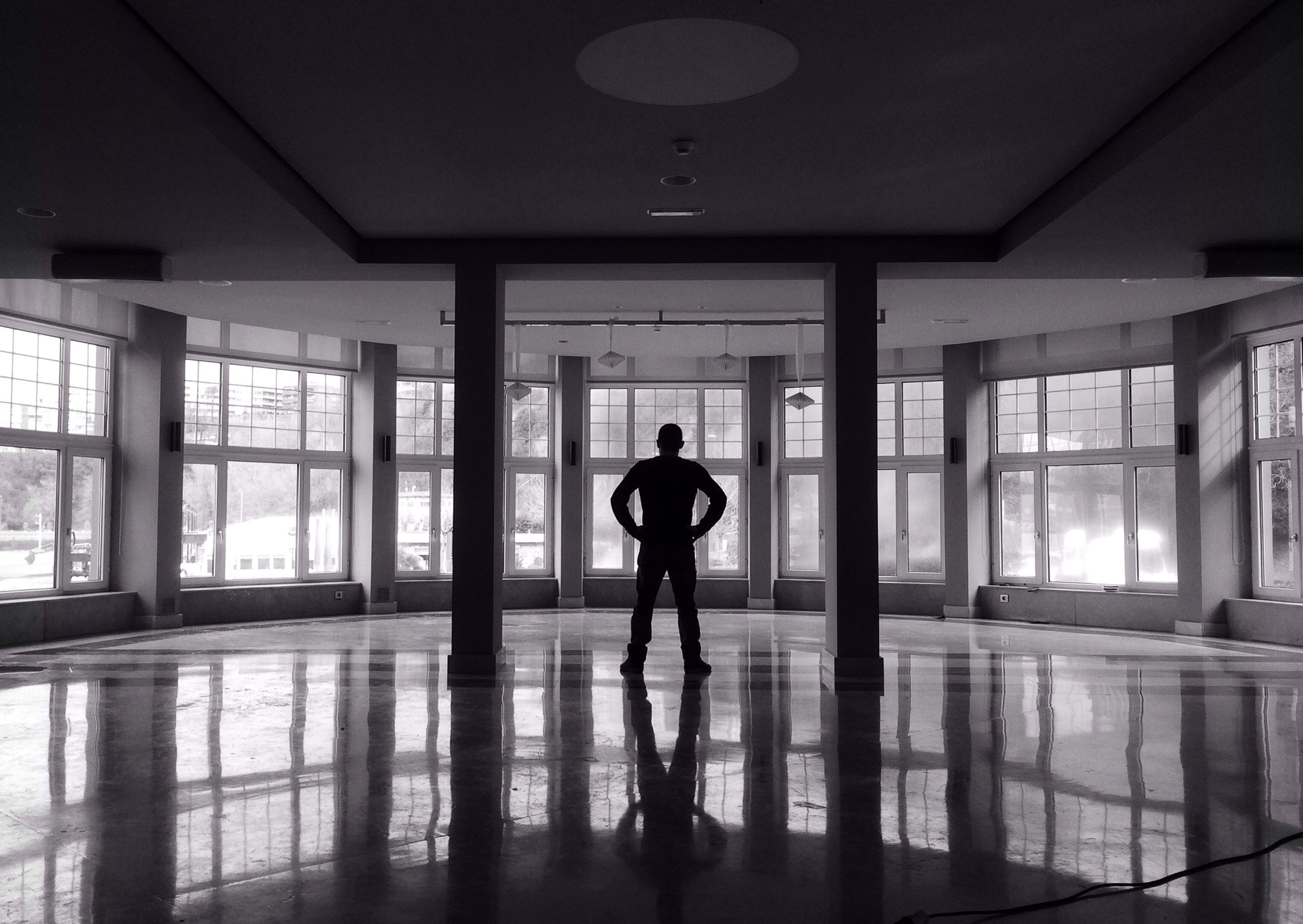 indoors, architecture, lifestyles, window, built structure, standing, full length, reflection, person, corridor, ceiling, leisure activity, flooring, men, glass - material, silhouette, rear view, walking