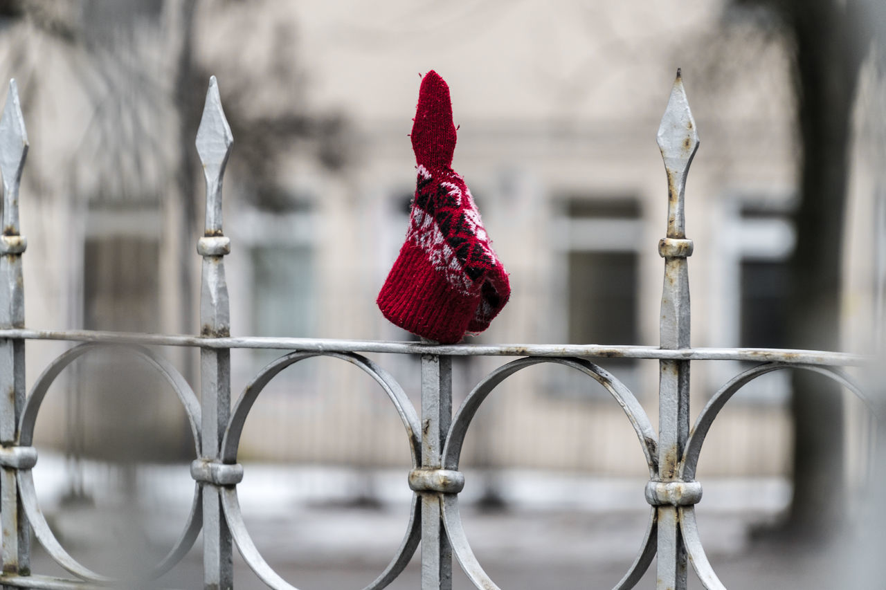 Red patterned ethnic glove / mitten / attached on the sharp, metal, fence spike. Attached City Culture Ethnic Fence Fencepost Fences Forgotten Glove Left Lithuanian Lost Mitten No Care Patterned Red Red Red Color Sharp Spike Spring Vilnius Wall Wear Winter