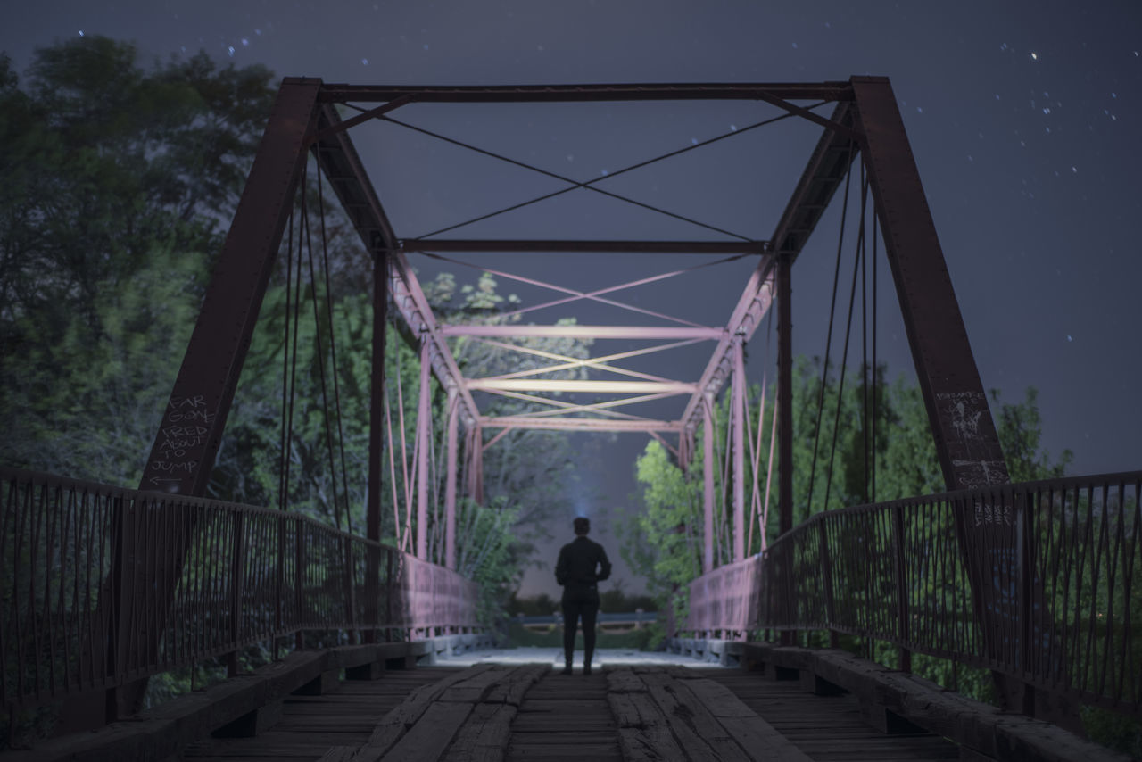bridge - man made structure, connection, rear view, the way forward, real people, architecture, one person, built structure, transportation, tree, men, outdoors, full length, nature, day, bridge, growth, lifestyles, footbridge, sky, people
