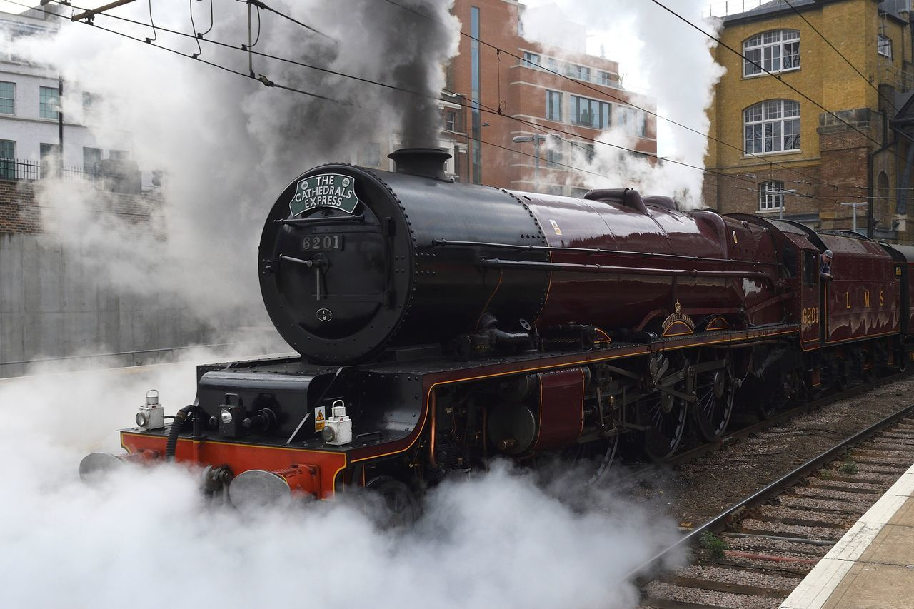smoke - physical structure, transportation, train - vehicle, rail transportation, steam train, mode of transport, locomotive, railroad track, public transportation, day, outdoors, steam, no people, building exterior, land vehicle, built structure, architecture, sky