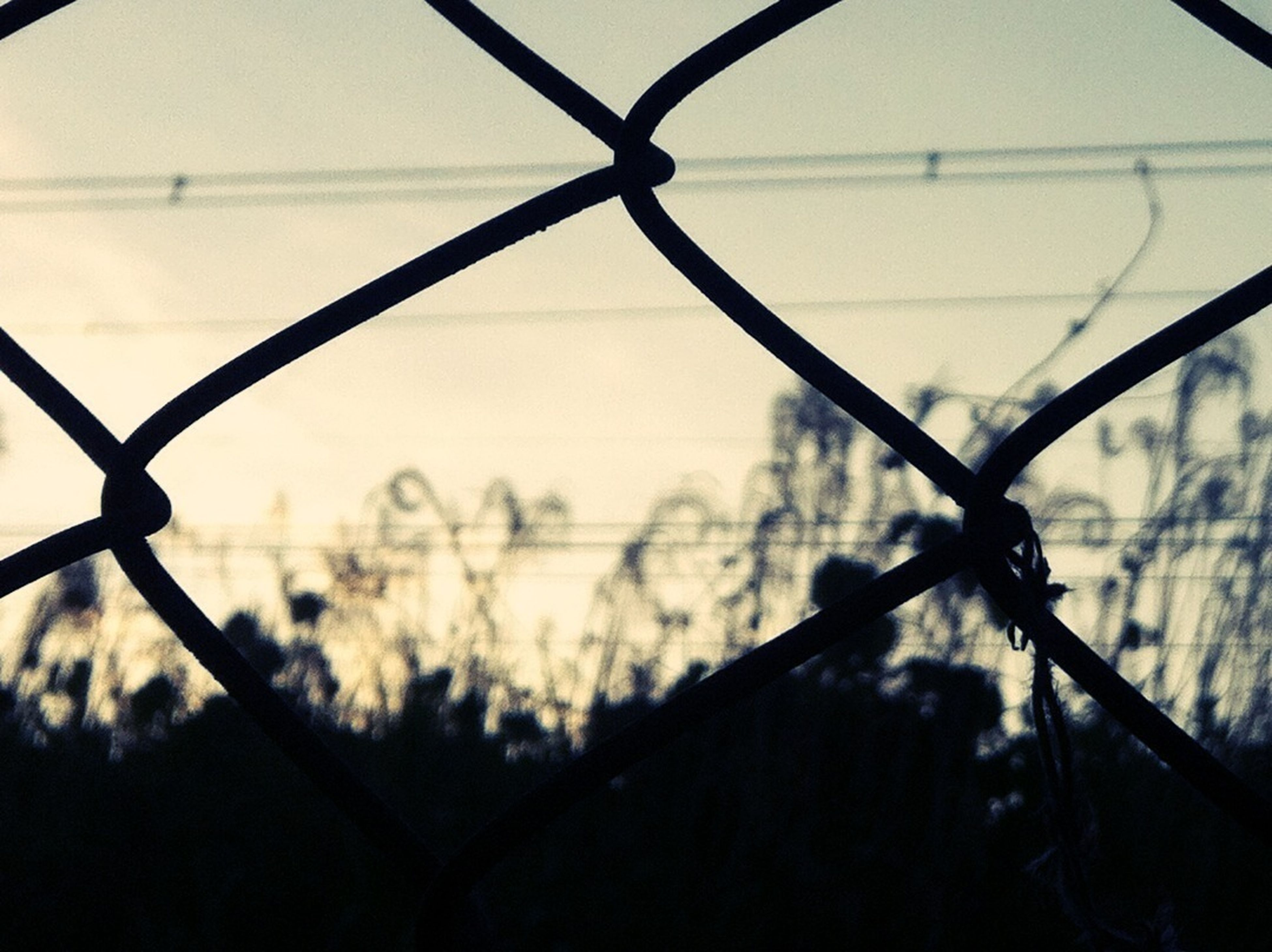focus on foreground, sky, protection, chainlink fence, safety, metal, close-up, sunset, fence, silhouette, security, no people, focus on background, outdoors, day, dusk, cloud - sky, transportation, transparent