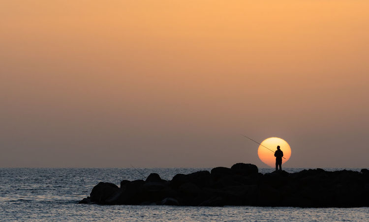 Silhouette Adult Amadores Beauty In Nature Breakwater Day Fishing Horizon Over Water Man Fishing Men Nature One Person Outdoors People Real People Rock - Object Scenics Sea Silhouette Sky Sun Sunset Tranquil Scene Tranquility Water