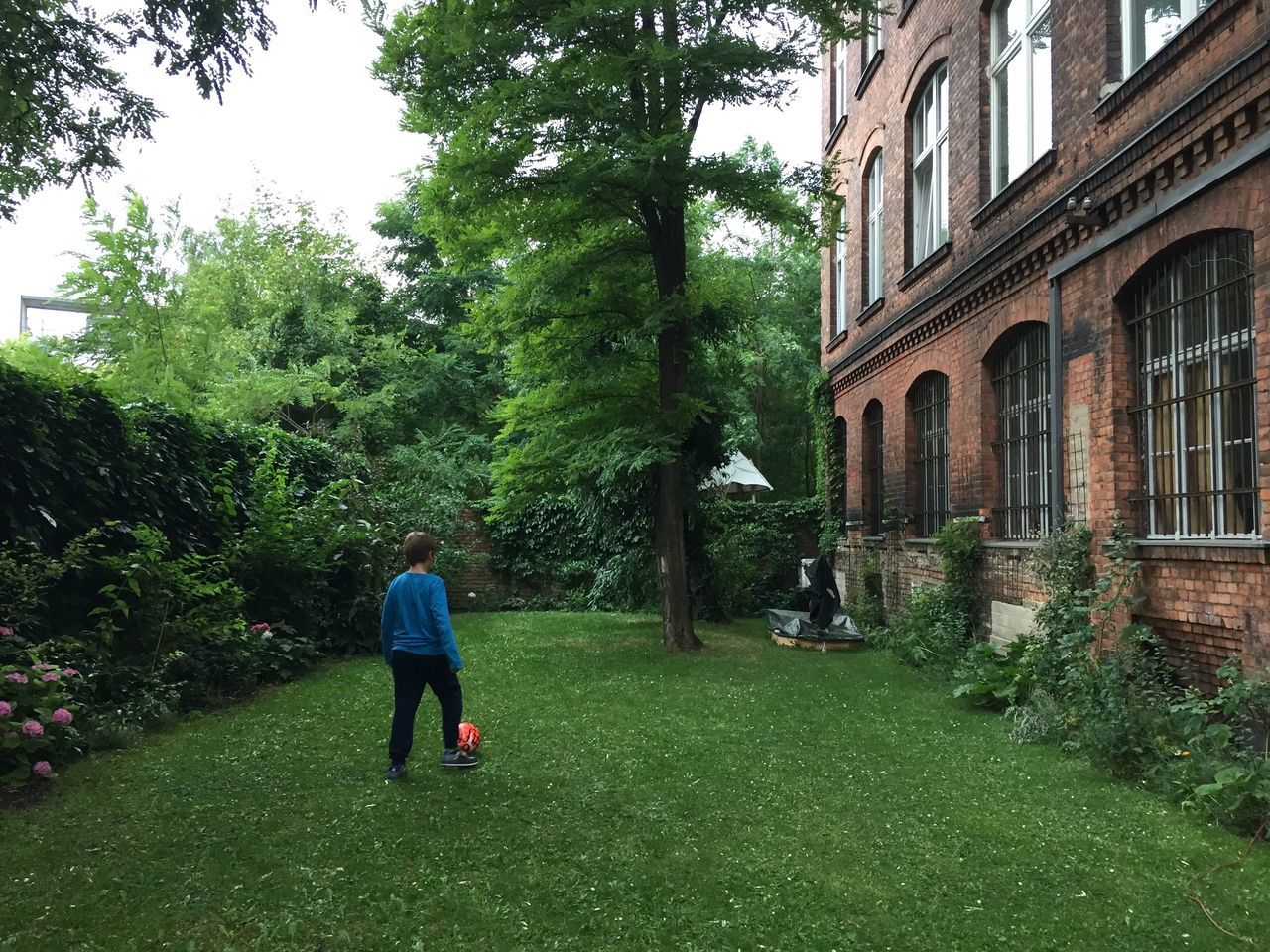Berlin Kreuzberg Achritechture Architecture Backyard Beauty In Nature Berlin Boy Day Football Full Length Grass Green Color Growth Kreuzberg Men Nature One Person Outdoors People Playing Real People Sky Tree