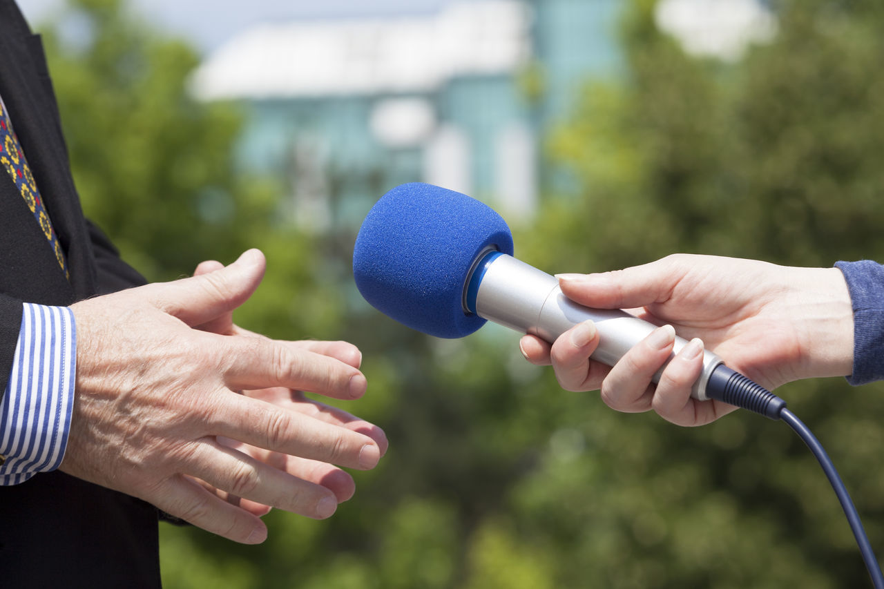 Journalist making media interview with politician Adult Broadcasting Business Close-up Day Event Holding Human Finger Human Hand Interview Light And Shadow Media Men Microphone Only Men People Politician Politics Press Radio Sport Taking Photos