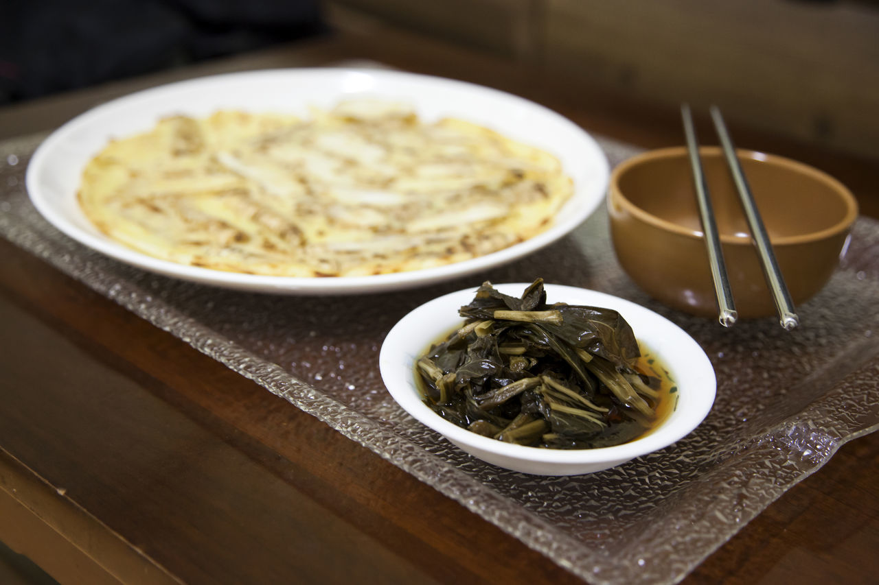 Jeon is like the pizza of Korean style. The food is Deodeok Jeon which is one of the traditional food in Ulleungdo Island. It is served with Makgeolli and bujigaengie namul. Bow Chop Stick Delicious Deodeokjeon Dish Food Food And Drink Freshness Indoors  Indulgence Korean Traditional Food Like Pizza Of Korean Style Makgeolli Meal Ready-to-eat Serving Size Tray