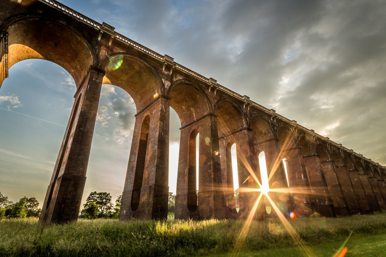 Arches Architecture Balcombe Viaduct Beauty In Nature Bridge - Man Made Structure Built Structure Cloud - Sky Connection Day Grass Lens Flare Nature No People Outdoors Red Brick Sky Starburst Sunset Train Travel Transportation Uk Viaduct Victorian Architecture West Sussex Wide Angle