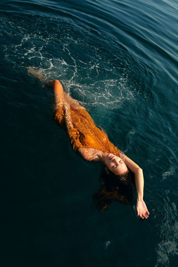 girl swimming in open water in clothes Beauty Beauty In Nature Blue Water Clean Water Day Floating On Water Girl Swimming Leisure Lying In Water Nature One Person Open Sea Open Water Orange Clothes Outdoors Real People Sea Summer Swimming Swimming In Clothes Swimming In Open Wate Swimming In The Sea Tanned G Water Young Adult
