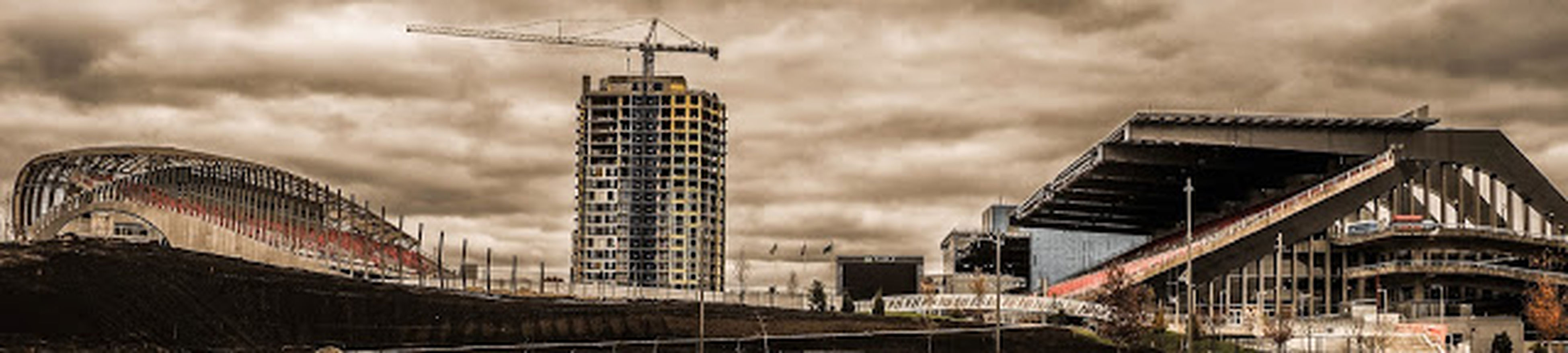 building exterior, architecture, built structure, crane - construction machinery, sky, construction site, development, city, cloud - sky, cloudy, industry, transportation, low angle view, construction, mode of transport, crane, construction industry, building, outdoors, day
