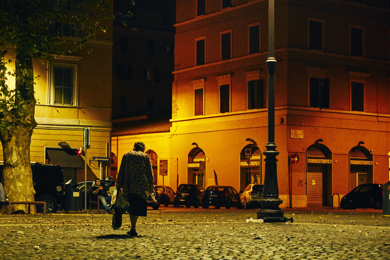 Rear View Of Senior Woman Walking On Street By Buildings At Night