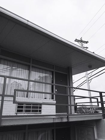 Cheap motel exterior Window Low Angle View Built Structure Architecture Building Exterior Bad Condition Obsolete No People Light And Shadow Monochrome Black & White Shapes And Forms Empty Railing Banality
