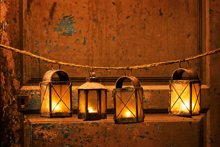 vintage candle lanterns in old house with antique wooden door, background Candle Flame Candle Light Candlelight Christmas Christmas Decorations Christmas Lantern Christmas Lights Noël Old House Old Objects Vintage Photo Wooden Door Xmas Xmas Decorations