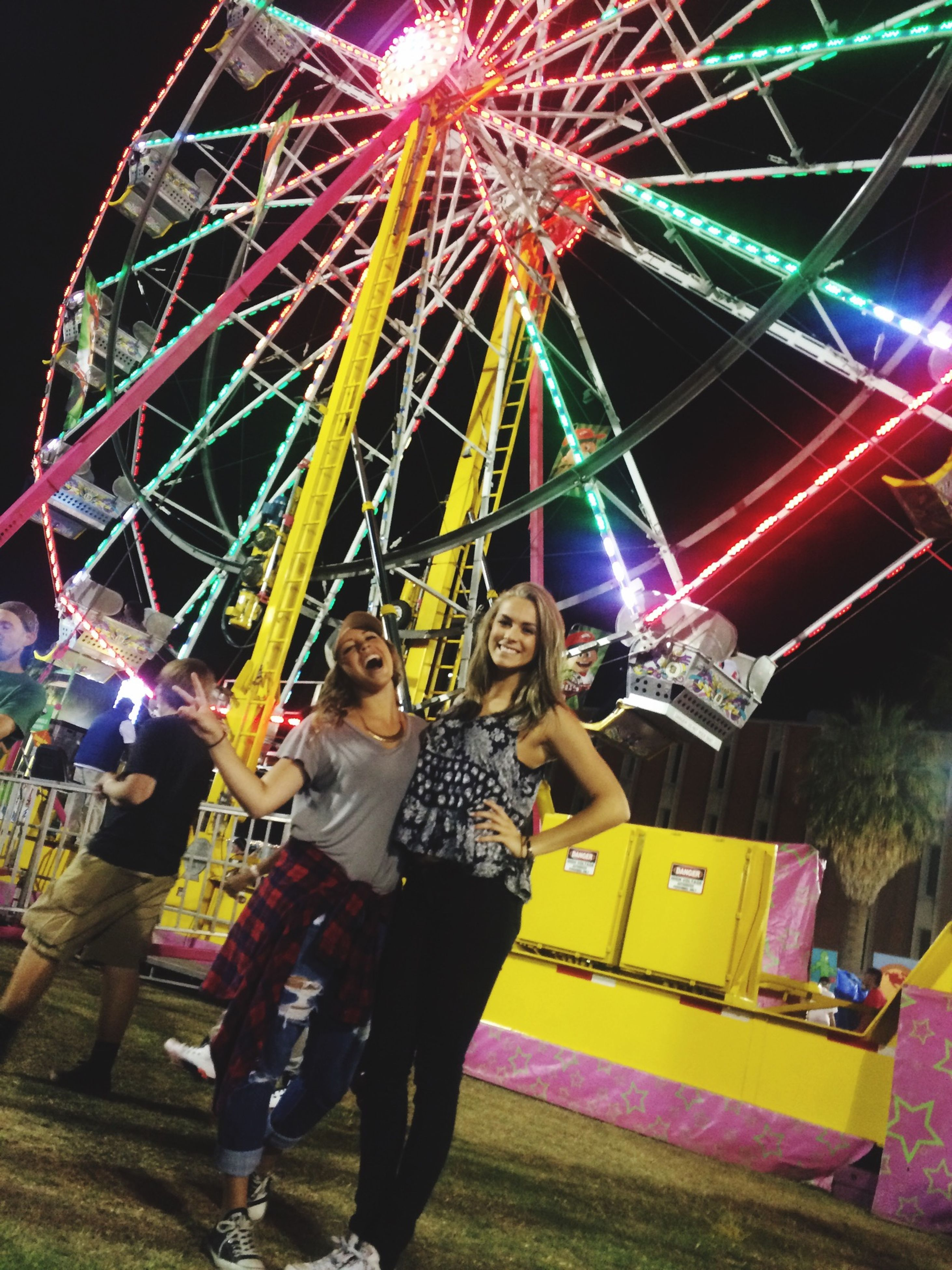 arts culture and entertainment, leisure activity, amusement park, amusement park ride, lifestyles, enjoyment, fun, ferris wheel, illuminated, men, celebration, holding, night, casual clothing, person, childhood, multi colored, standing