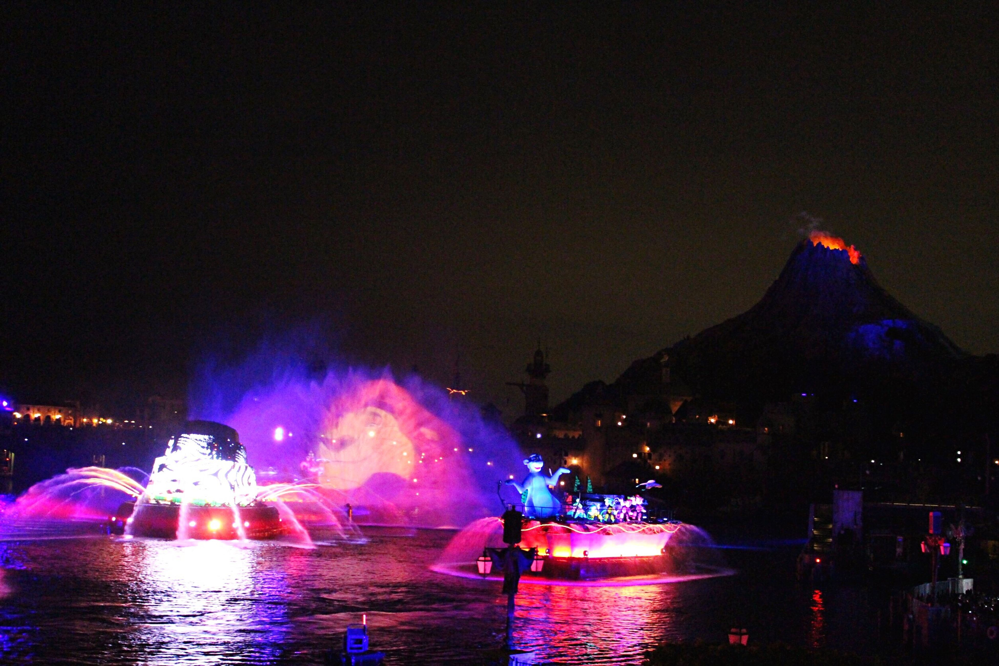 illuminated, night, water, waterfront, travel destinations, fountain, sky, multi colored, tourism, sea, outdoors, city life, pink color, dark, harbor, famous place, vacations, scenics, firework - man made object