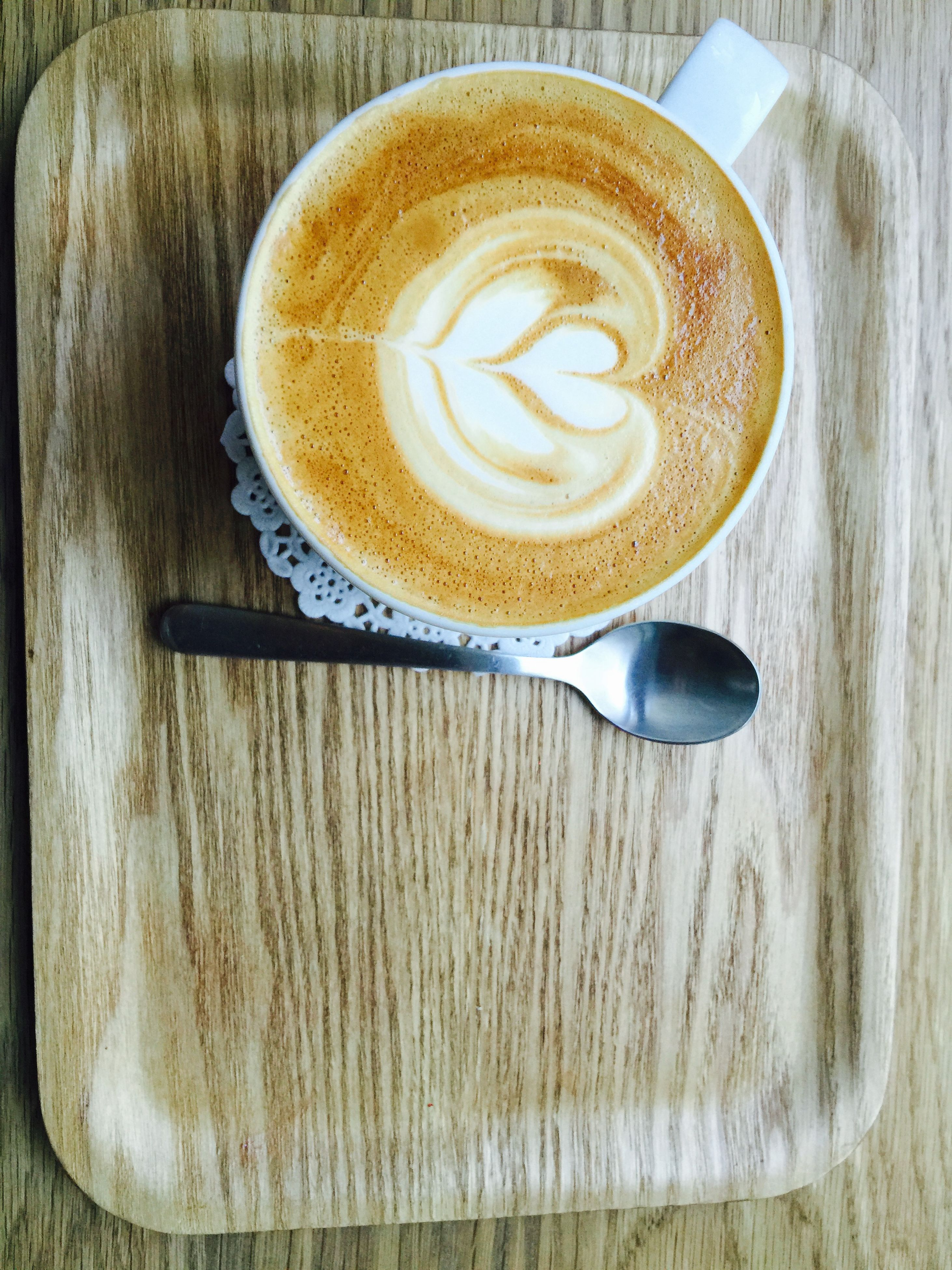 food and drink, coffee cup, table, coffee - drink, drink, refreshment, indoors, still life, saucer, frothy drink, freshness, high angle view, cappuccino, froth art, coffee, directly above, spoon, wood - material, close-up, heart shape