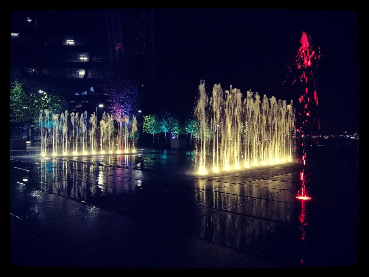 night, illuminated, fountain, transfer print, motion, celebration, water, lighting equipment, city, spraying, building exterior, glowing, multi colored, decoration, modern, outdoors, event, splashing, exploding, tourism
