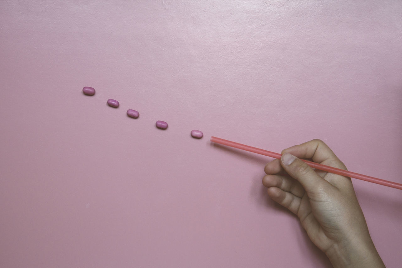 Cropped Hand Holding Drinking Straw By Candies Over Table