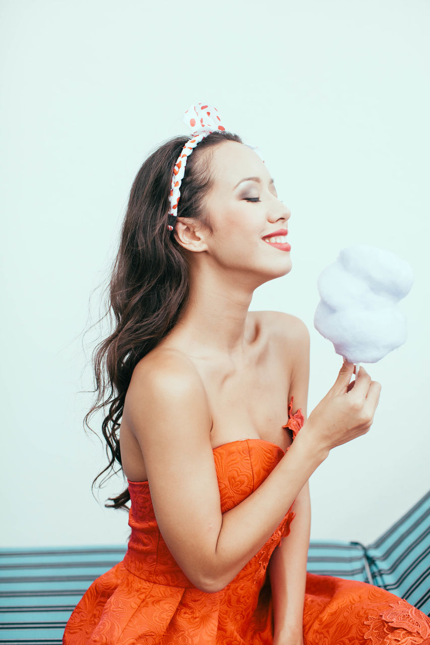 Smiling Woman Holding Cotton Candy Against White Background