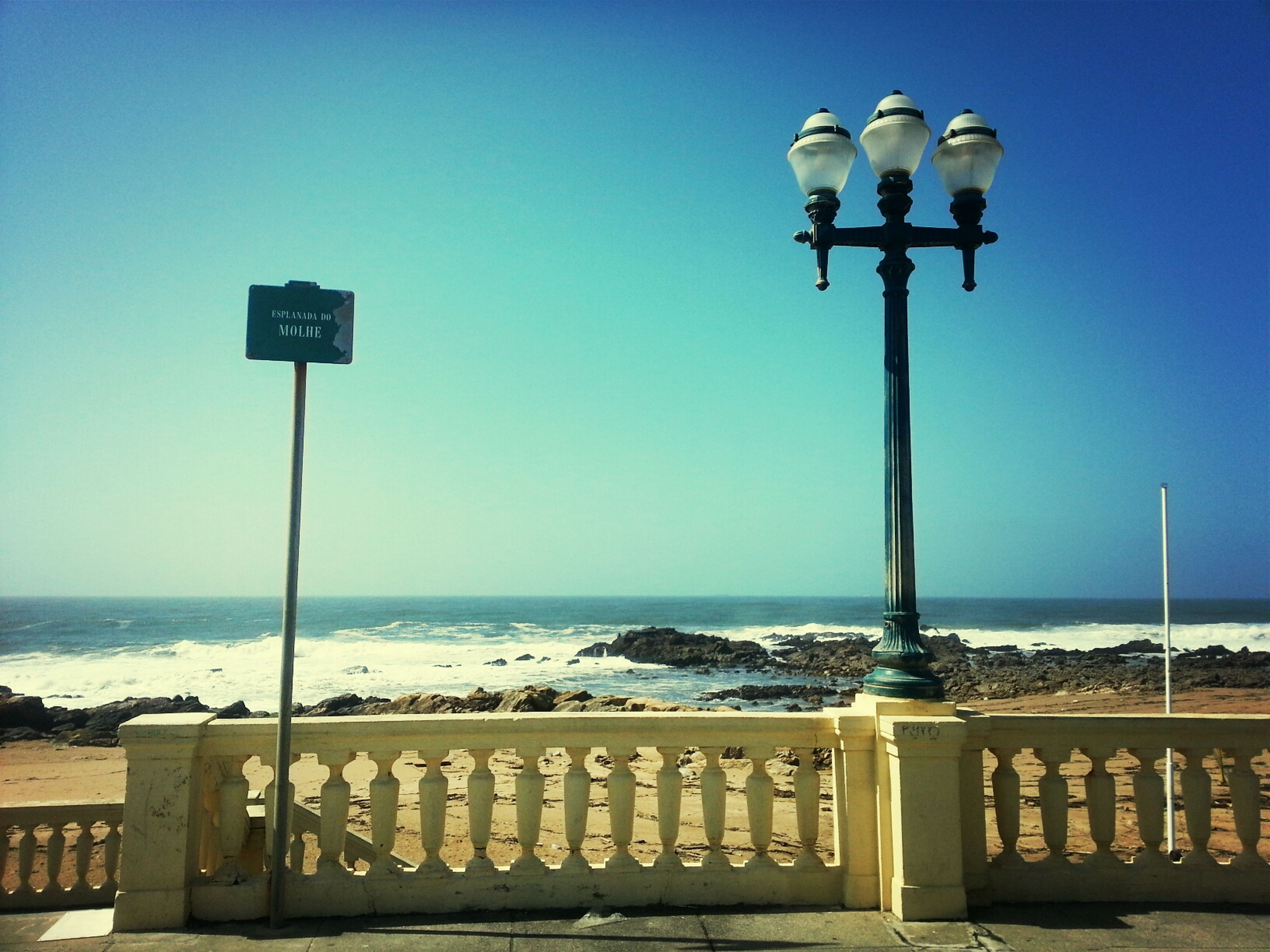 sea, clear sky, horizon over water, street light, water, lighting equipment, guidance, text, blue, copy space, pole, communication, information sign, sign, western script, tranquility, beach, lamp post, tranquil scene, nature