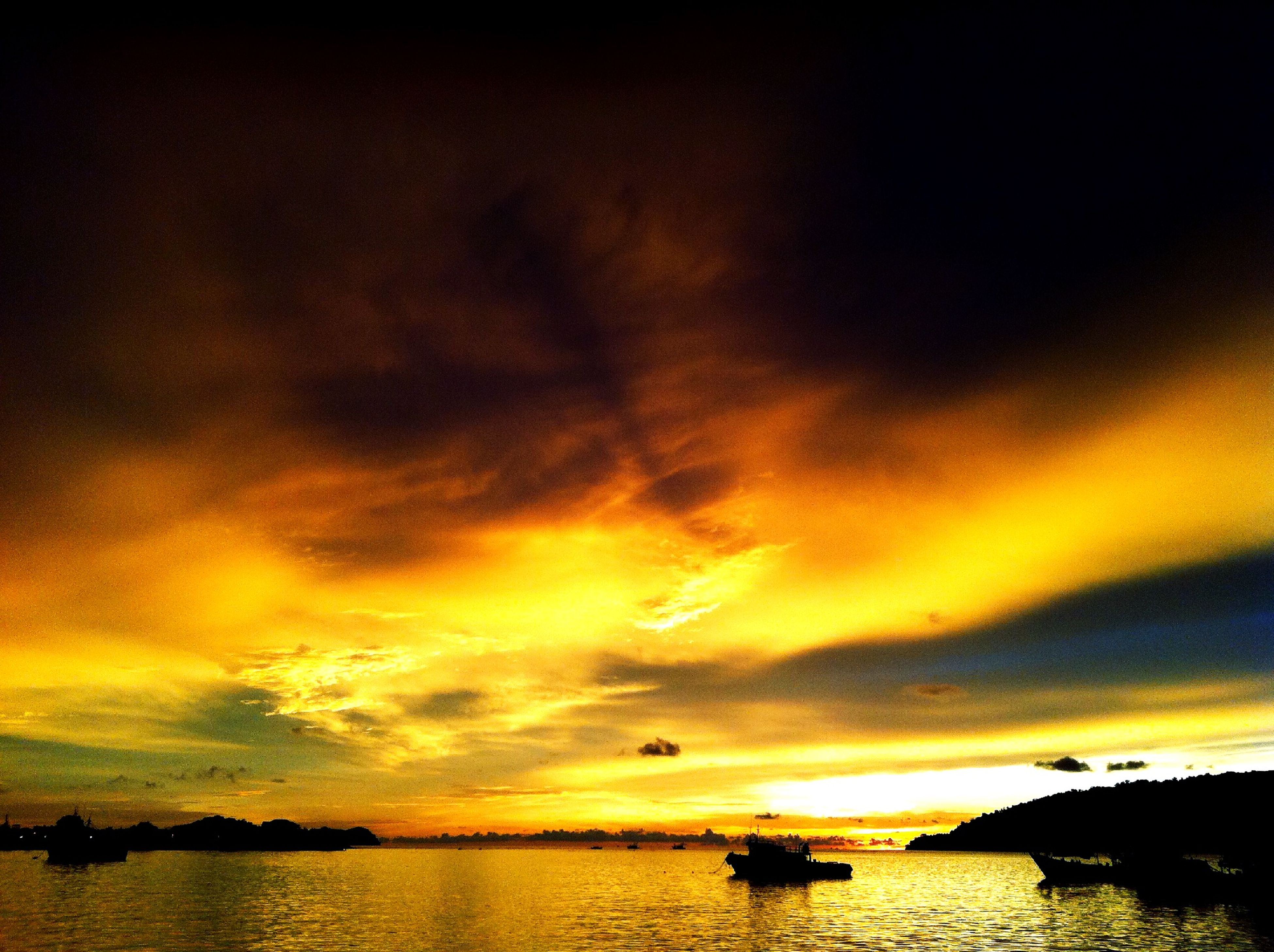 sunset, water, sky, scenics, beauty in nature, tranquil scene, sea, tranquility, cloud - sky, orange color, silhouette, idyllic, waterfront, dramatic sky, cloud, cloudy, nature, horizon over water, reflection, sun