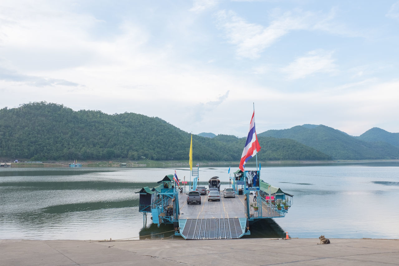 Thai Flag On Ferry With Cars Moored At Lake