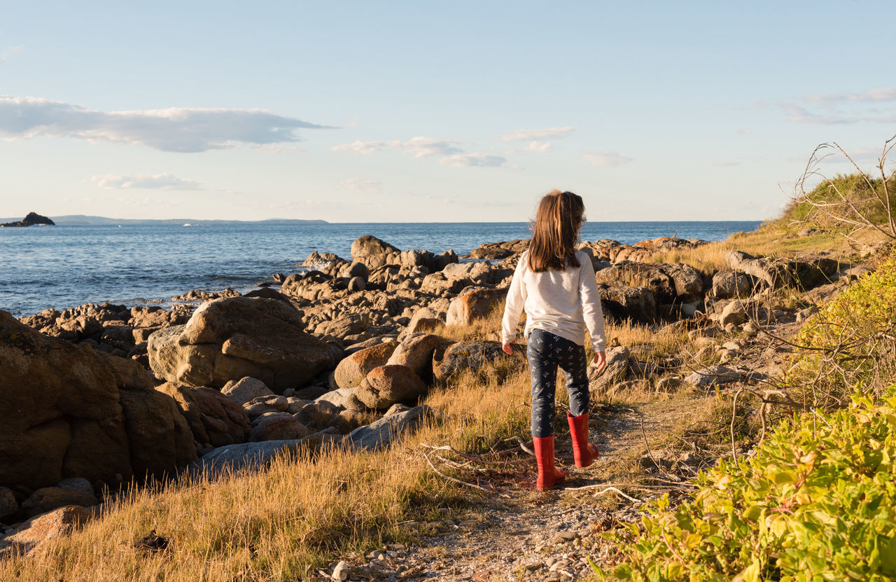 Little girl walking by the ocean in winter with afternoon sunshine Beach Beauty In Nature Casual Clothing Childhood Day Full Length Girl Grass Horizon Over Water Leisure Activity Lifestyles Long Hair Nature One Person Outdoors People Real People Rear View Rock - Object Scenics Sea Sky Standing Sunlight Water