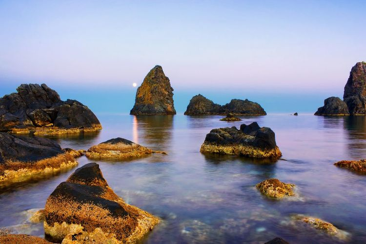 Dreamscape Sea Tranquil Scene Scenics Beauty In Nature Water Tranquility Nature Rock Formation Idyllic Faraglioni Acitrezza  Clear Sky Sky No People Calm Horizon Over Water Sicily Beach Boulder - Rock Day Landscapes Landscape Betterlandscapes Landscape_Collection Traveling EyeEm Selects