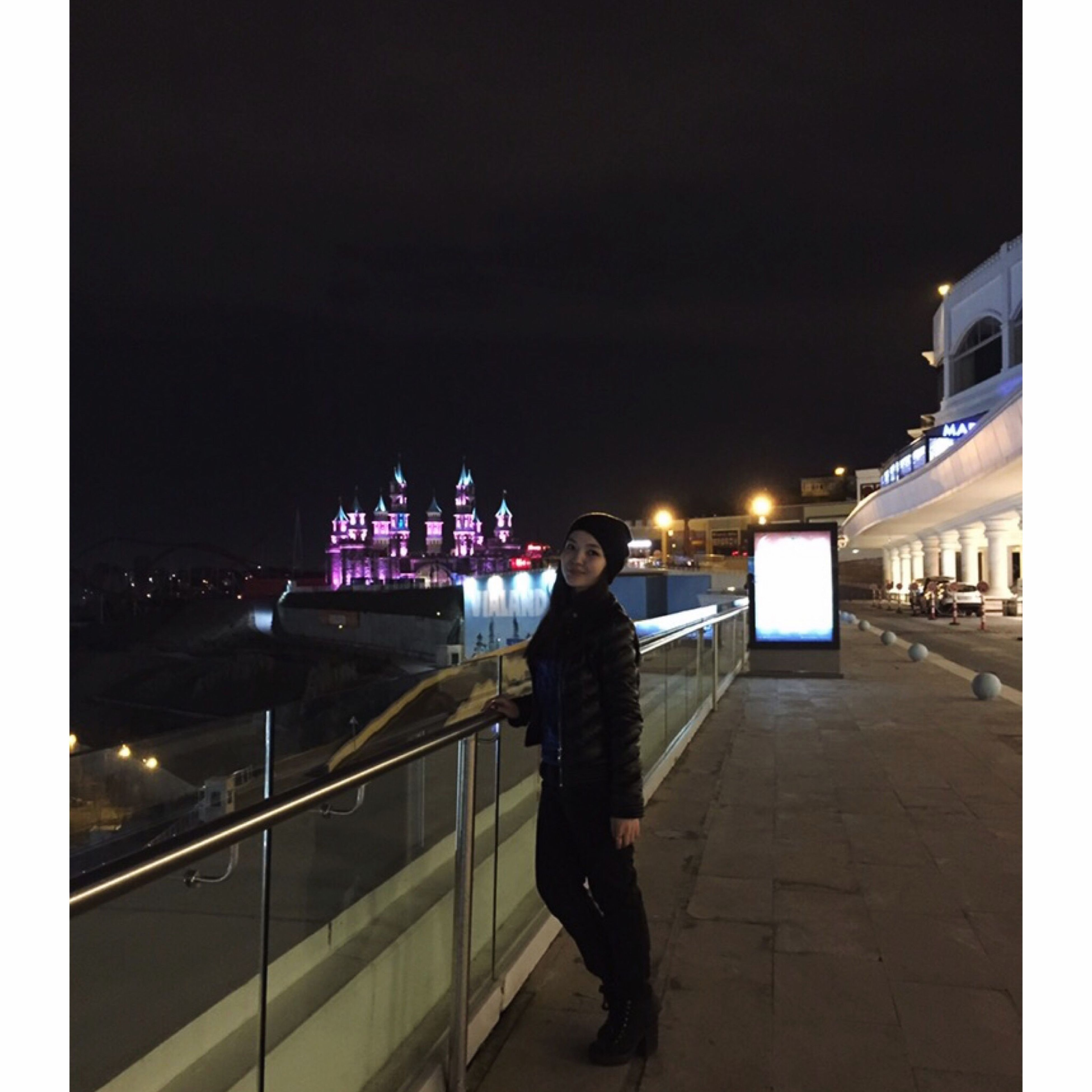 night, illuminated, architecture, building exterior, built structure, lifestyles, standing, leisure activity, rear view, city, full length, men, casual clothing, sky, city life, person, walking, railing