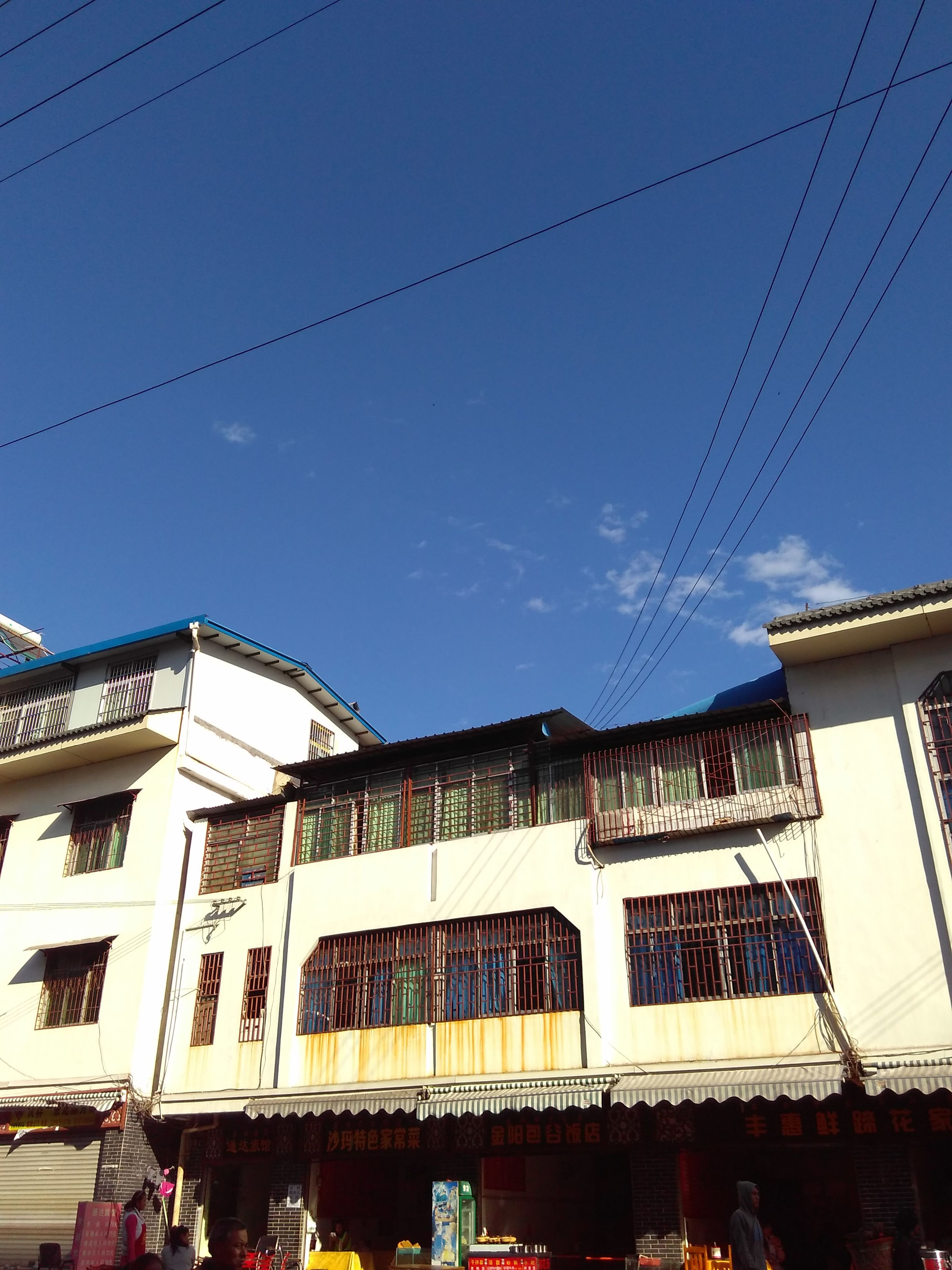 building exterior, architecture, built structure, low angle view, power line, residential building, cable, window, residential structure, building, house, clear sky, sky, blue, hanging, day, outdoors, city, no people, electricity