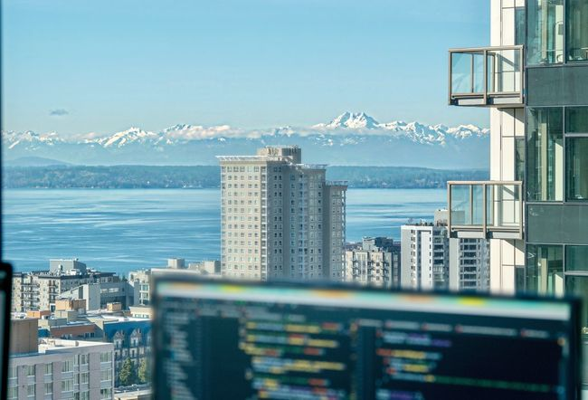 Coding with a view City Building Exterior Architecture Skyscraper Cityscape Built Structure Sea Water Sky Day Urban Skyline No People Outdoors Downtown District Modern Nature Beauty In Nature Code Coding Programming Software Computer Monitor Mountain Mountain Range